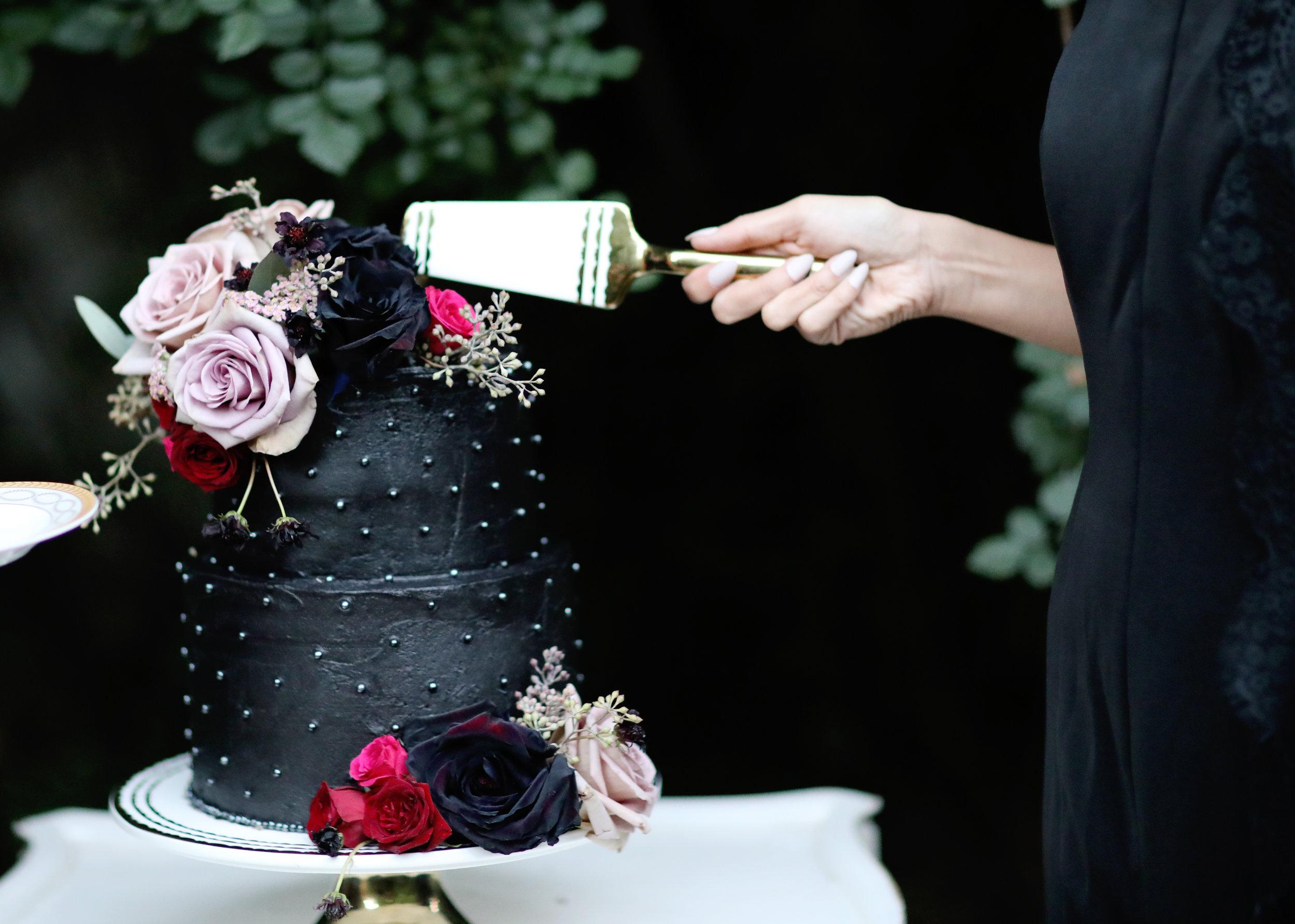 Black wedding cake with vintage rental cake plate and matching cake server.