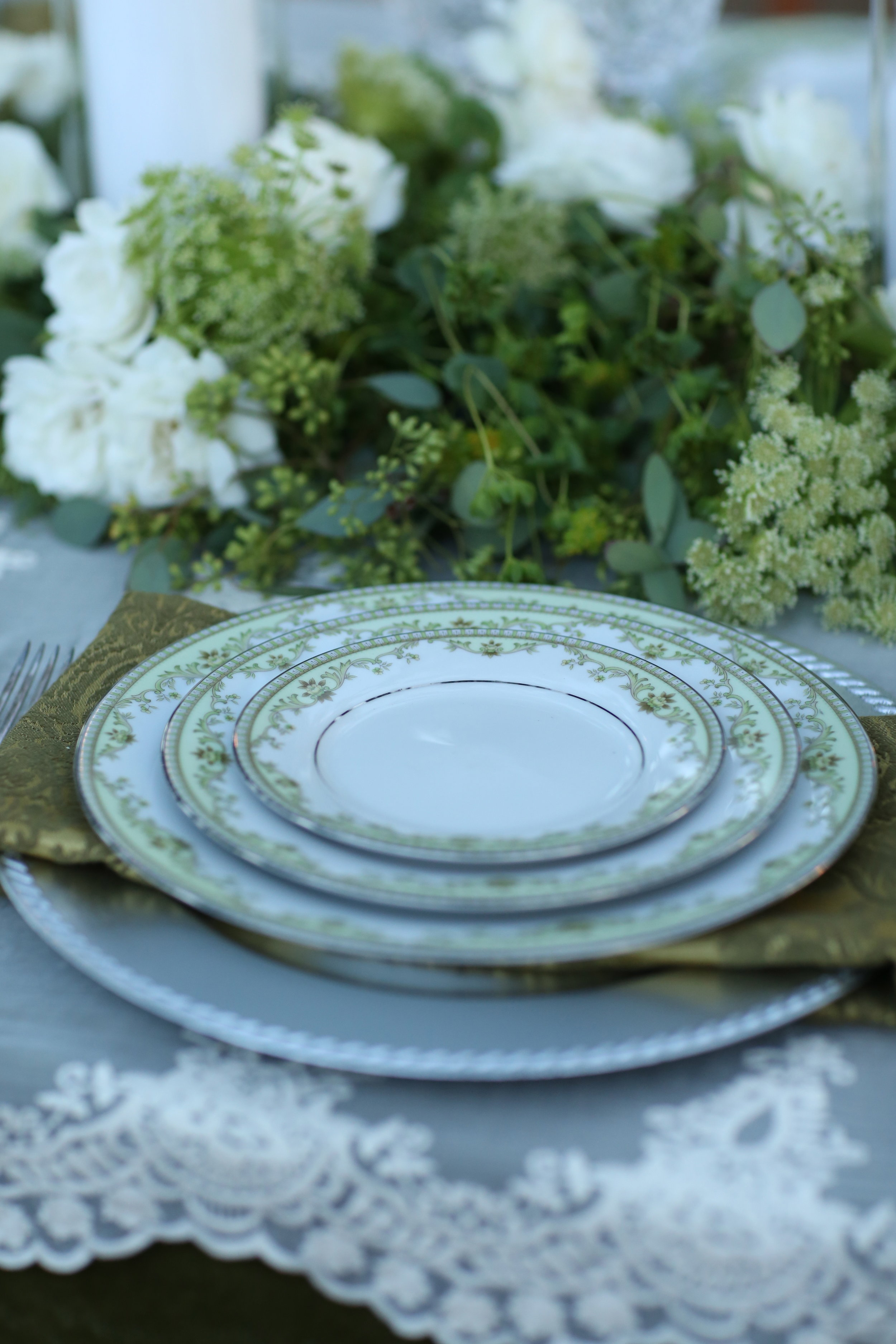 Charger plate anchors the rest of the vintage china used on a wedding table.