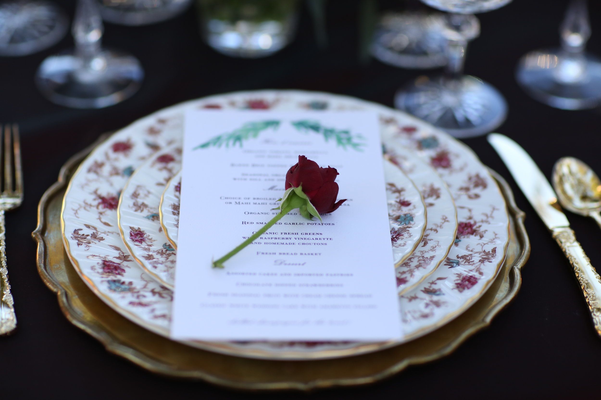 Brass charger plate anchoring the floral vintage china table setting during a wedding.