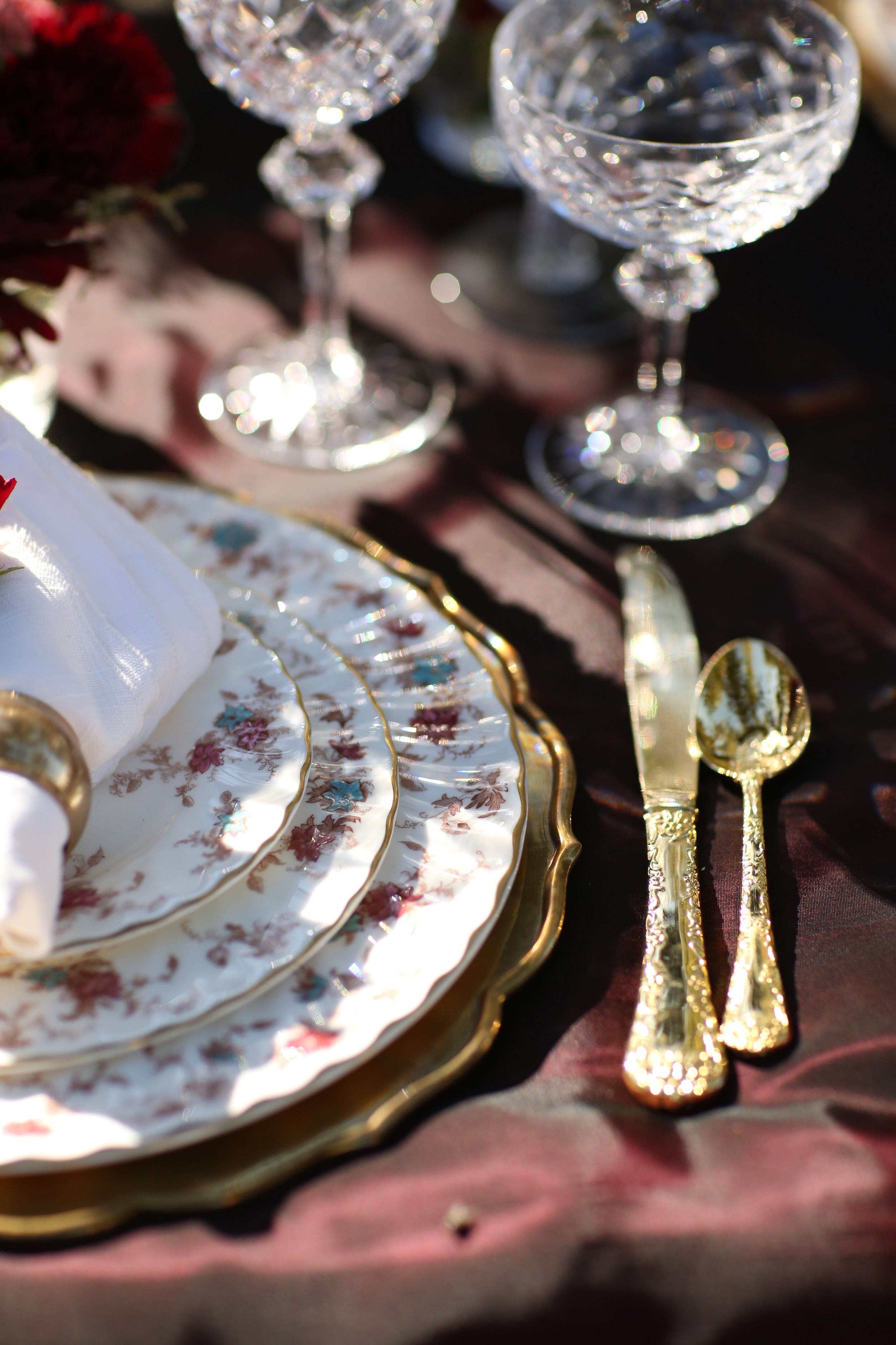 Gold silverware enhancing a wedding table setting of vintage china set on a brass charger plate.
