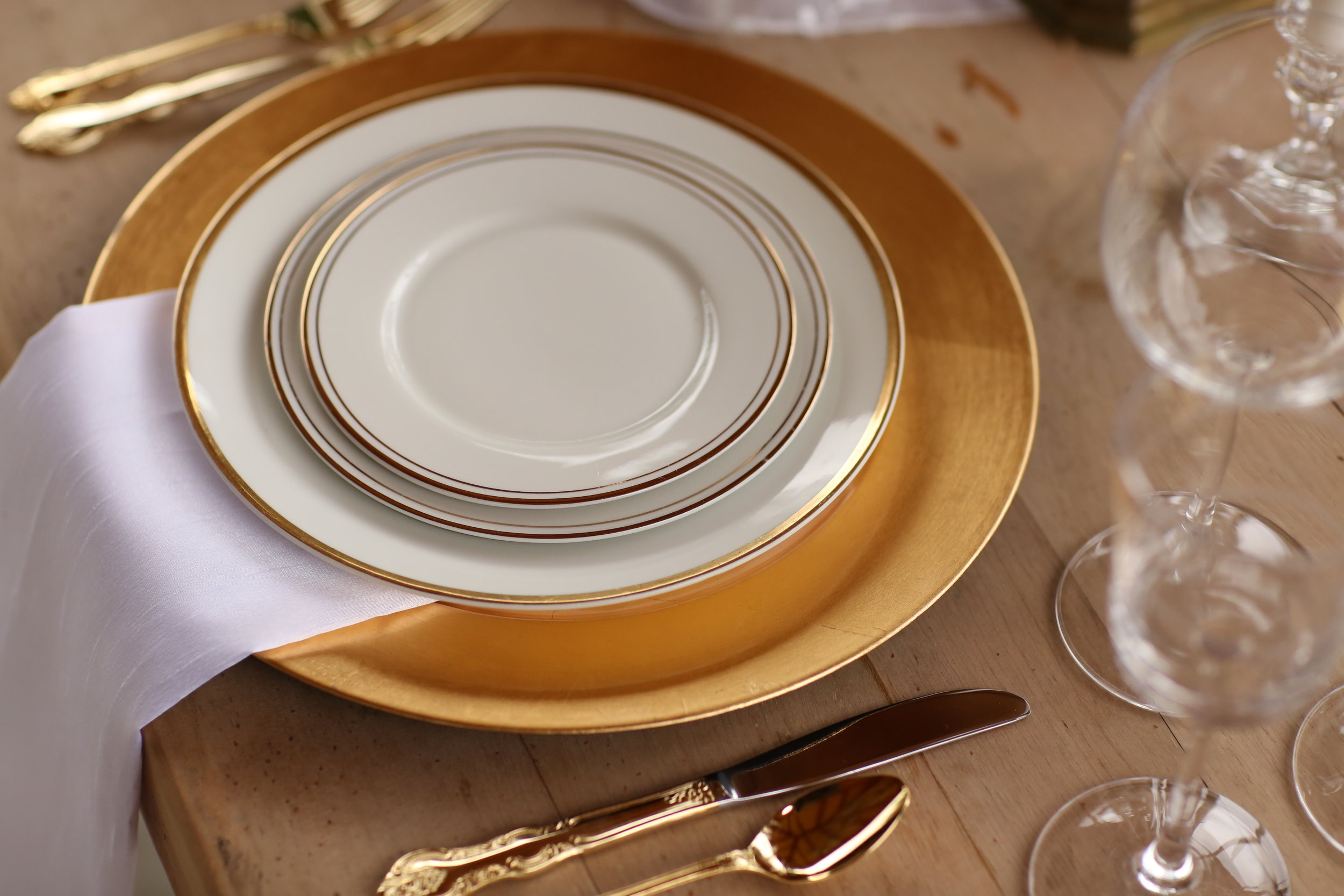 Gold charger plate with gold rimmed china, gold silverware, and vintage crystal goblets set for a wedding table. Vintage rentals from Birdie in a Barn.