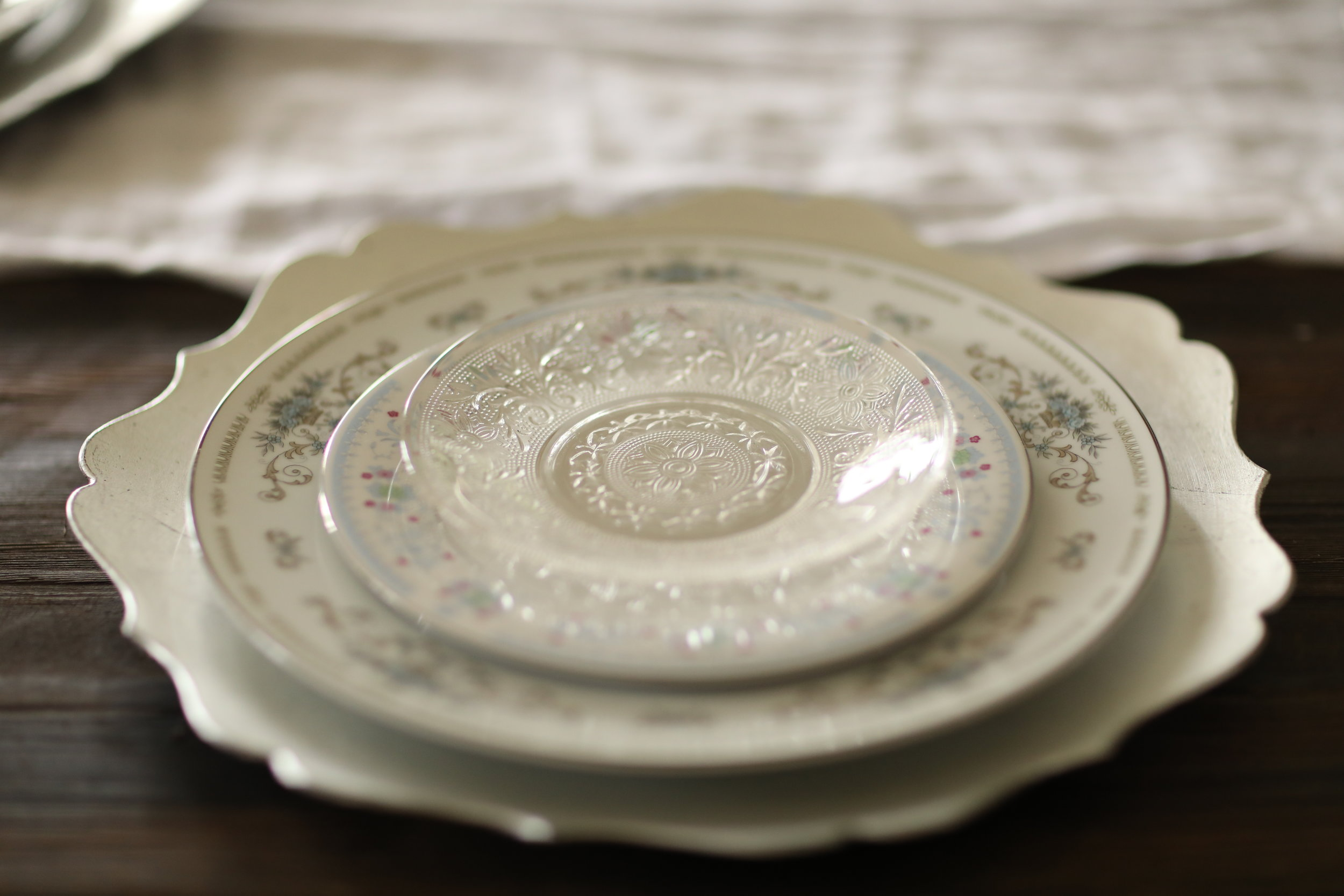 Scalloped charger plate under vintage mismatched china.