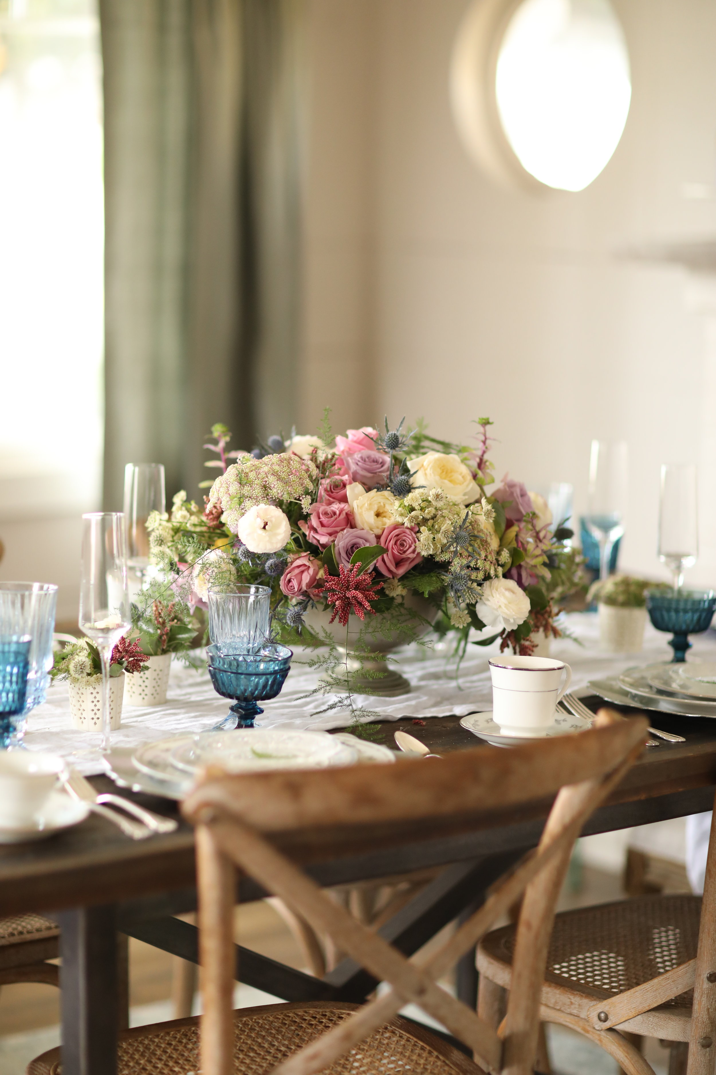 Table setting with blue goblets and vintage mismatched china on top of ceramic charger plates.