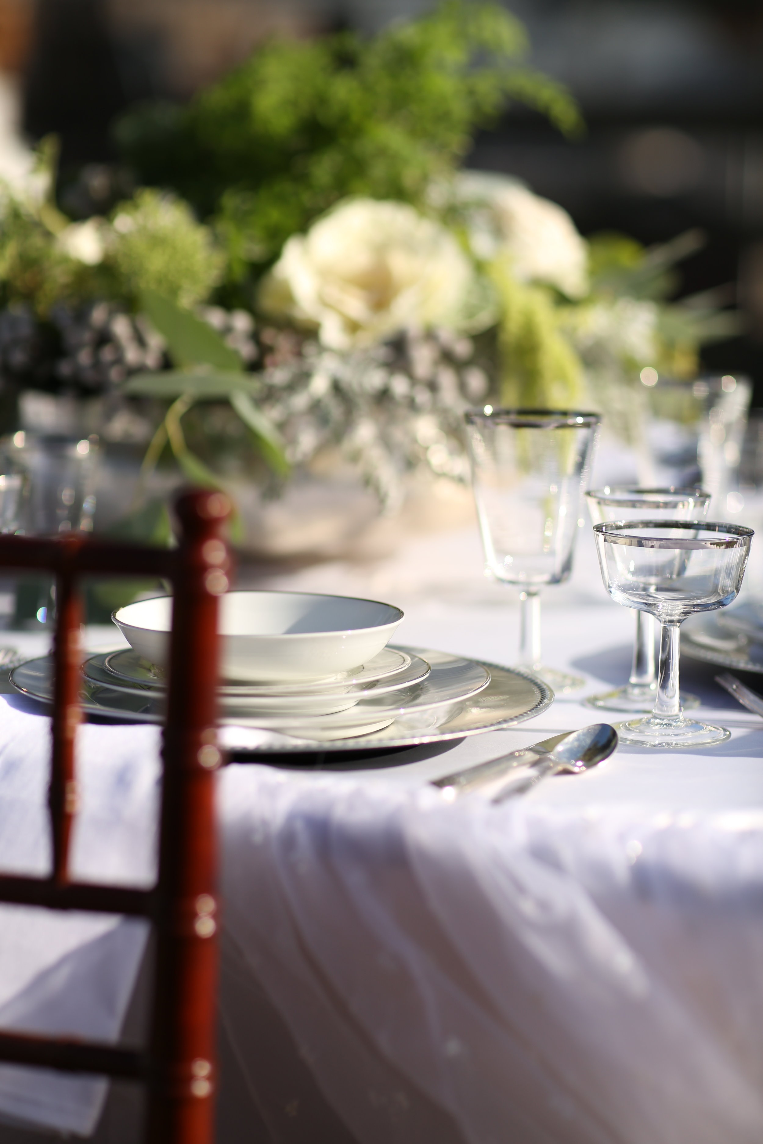 Silver charger plates set on a wedding table.