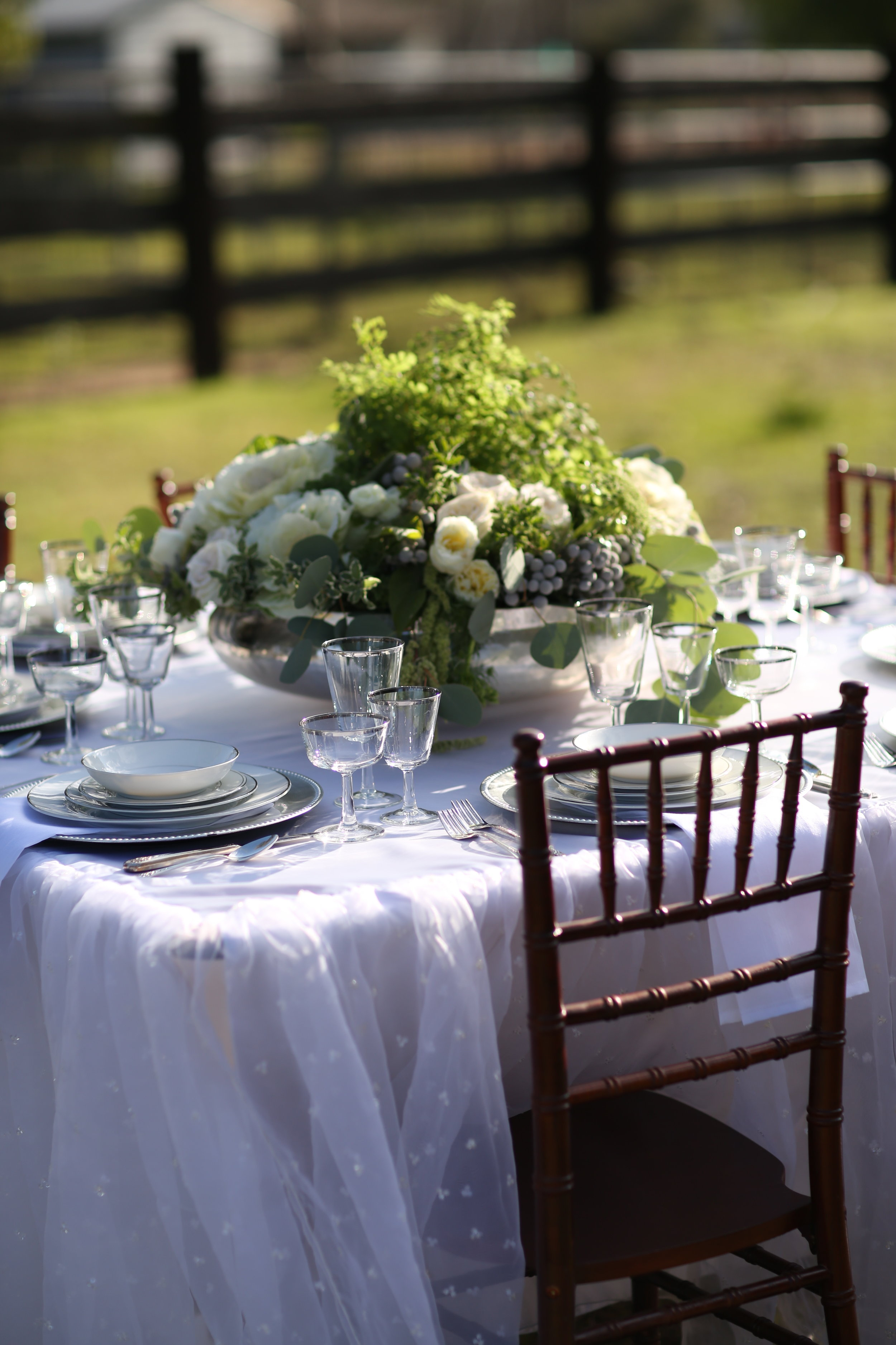 Silver charger plates with vintage china on a wedding table.