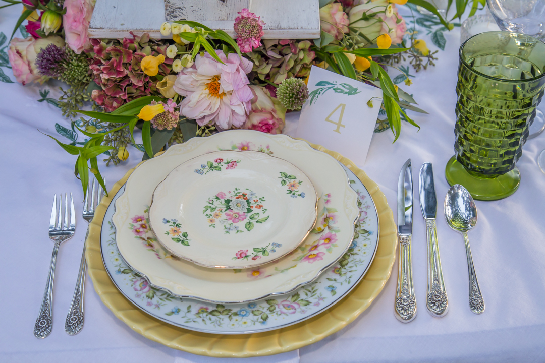 Yellow charger plate with vintage mismatched china.