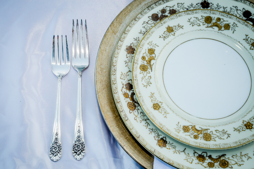 Close up of gold charger plate with vintage china and silverware.