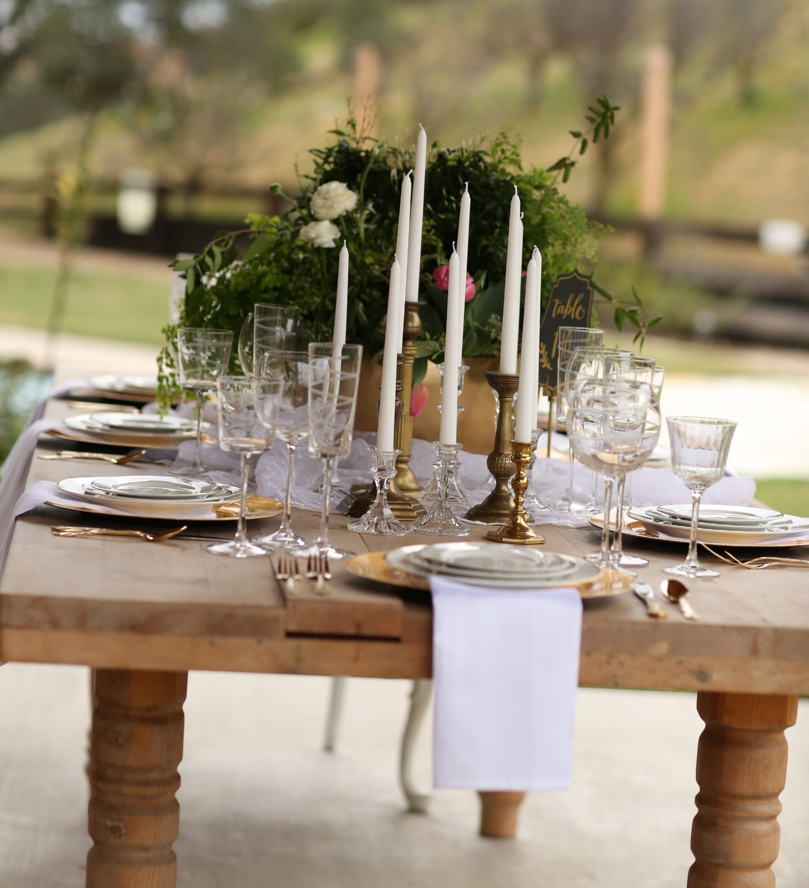 Farm table set with gold china, crystal, and gold chargers. Vintage rentals in Murrieta. Photo taken at Chateau Adare.