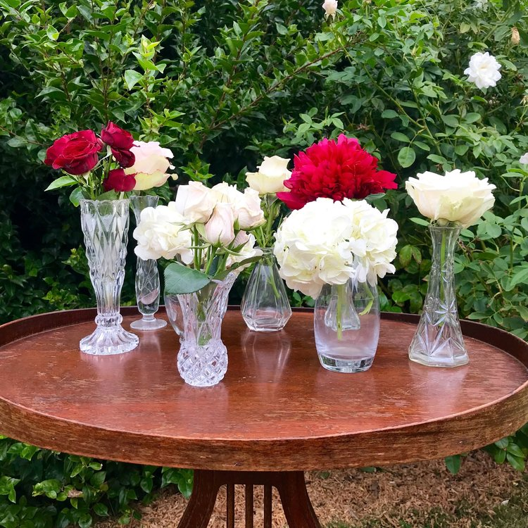 Assorted small cut glass vases with red and white flowers.