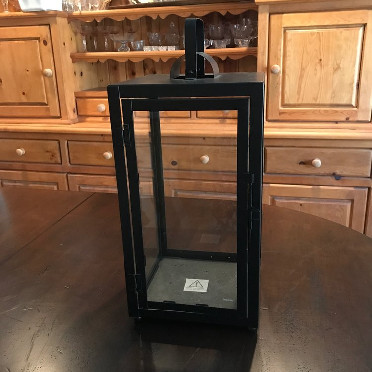 """Extra Large Black Lantern   Matte black metal lantern with glass sides. Openable door on one side. Handle can be used for hanging. 24.5"""" tall x 12"""" square. Comes with three candles in glass."""