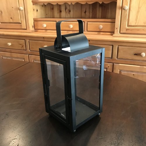 """Small Black Lantern   Matte black metal lantern with glass sides. Openable door on one side. Handle can be used for hanging. 12"""" tall x 6"""" square. Comes with three candles in glass."""