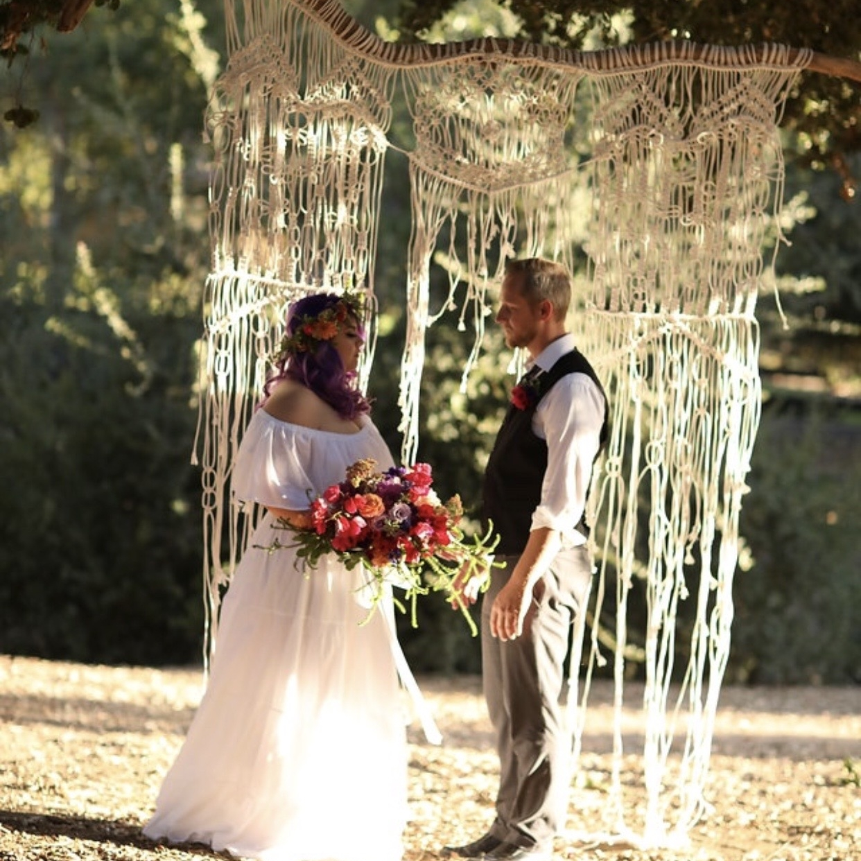 Bride and groom in front of a. macrame backdrop hanging from a tree at Chateau Adare.