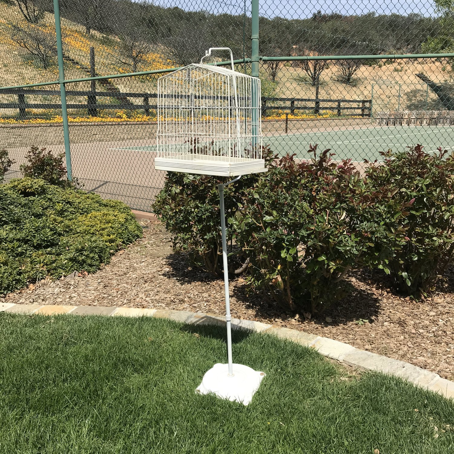 Metal birdcage on a free standing stand.