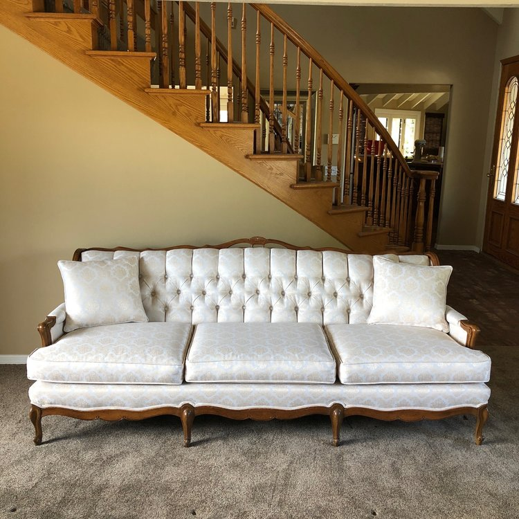 "Chloe   Tufted, rolled back, three cushion, wood trimmed, cream embossed damask couch. French Provincial feet, four in front. 82"" long x 36"" wide x 33"" high. Perfect for lounge areas."