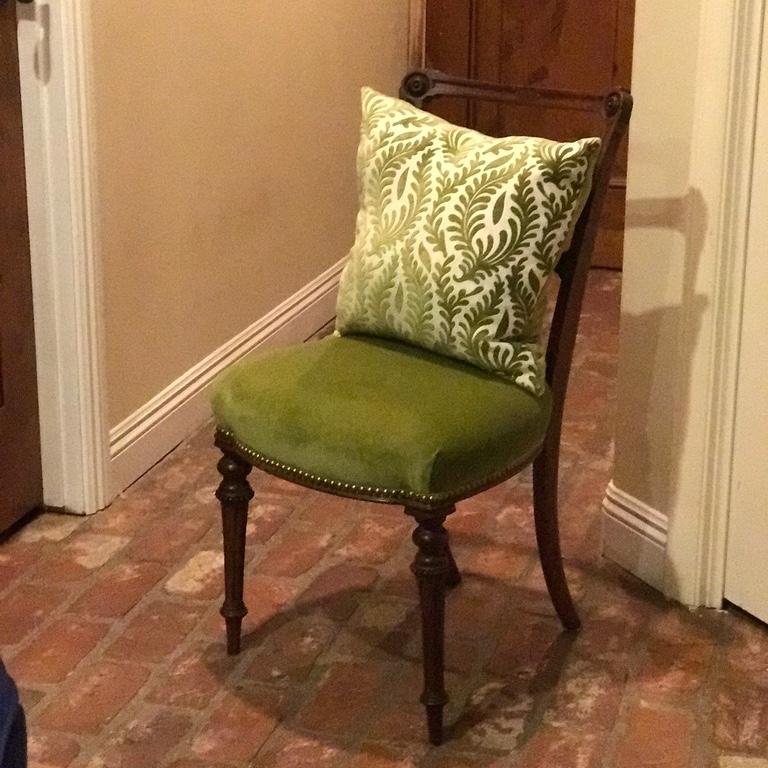 Petite green velvet chair with throw pillow.