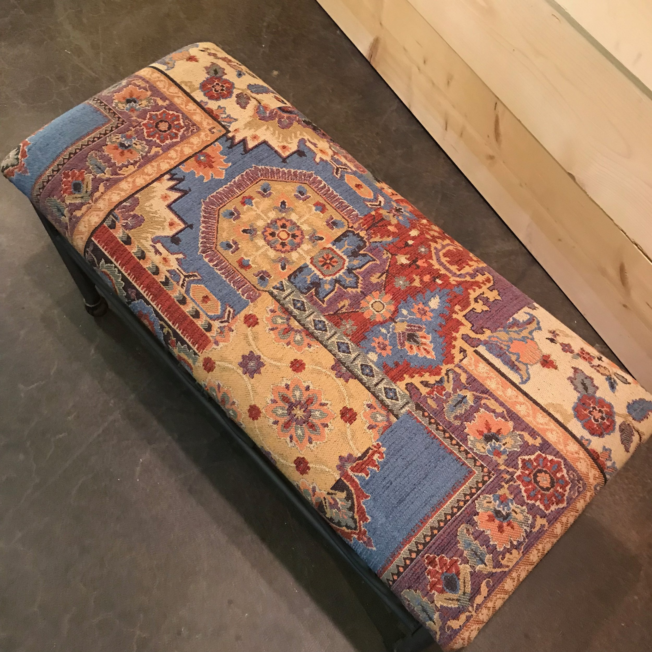 Tapestry fabric on the top of a metal scrolled bench.