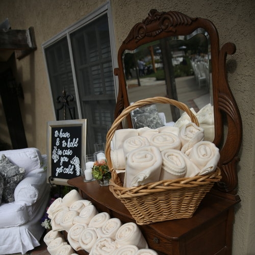 Low boy dresser with vintage mirror used for blankets at a wedding reception.