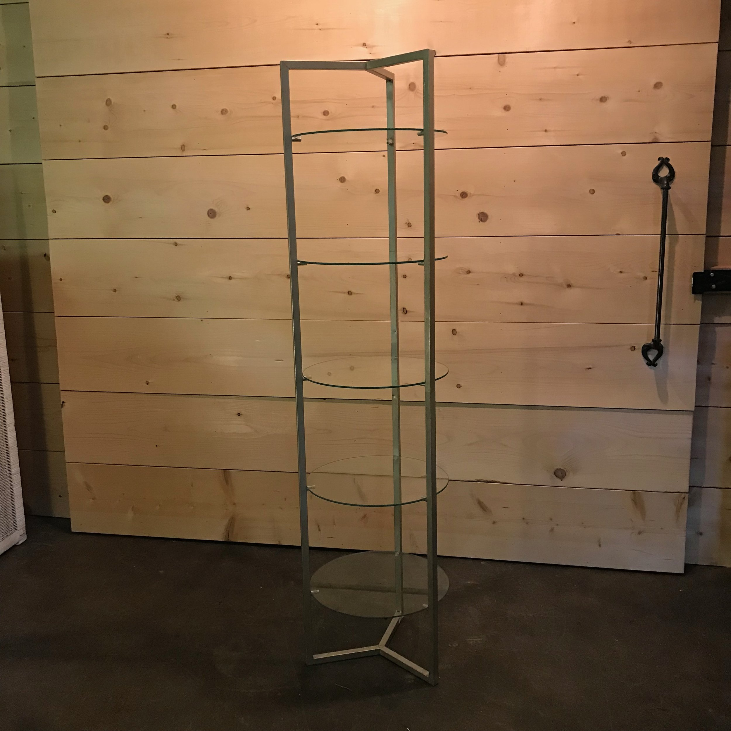 "Dudley   Brass etagere with five round glass shelves that are 17"" in diameter. The overall height of the shelving is 64"" tall. Perfect for displaying all kinds of delicacies."