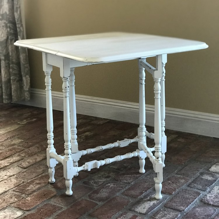 """Megan   Shabby Chic white double drop leaf table with spindle legs. Makes a fantastic cake table. 26"""" long x 11"""" wide with sides down, or 30"""" wide with sides up. 26.5"""" tall."""