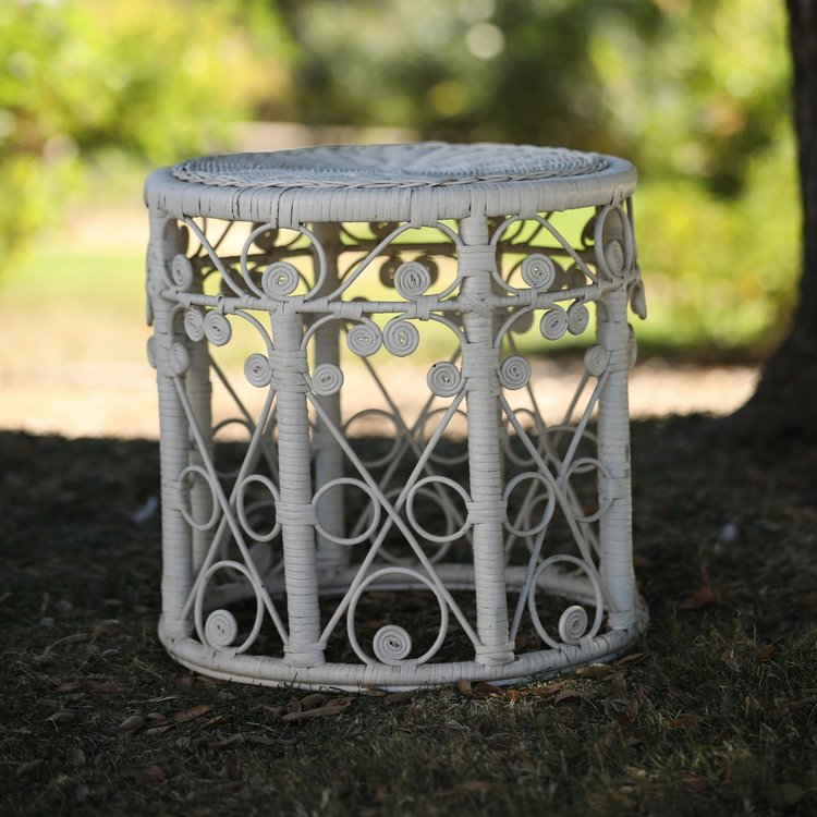 """Miranda   White wicker table. 18"""" round by 18"""" high. Delicate scrolled design on the side of the table in swirling patterns. Great for that Boho Bride."""