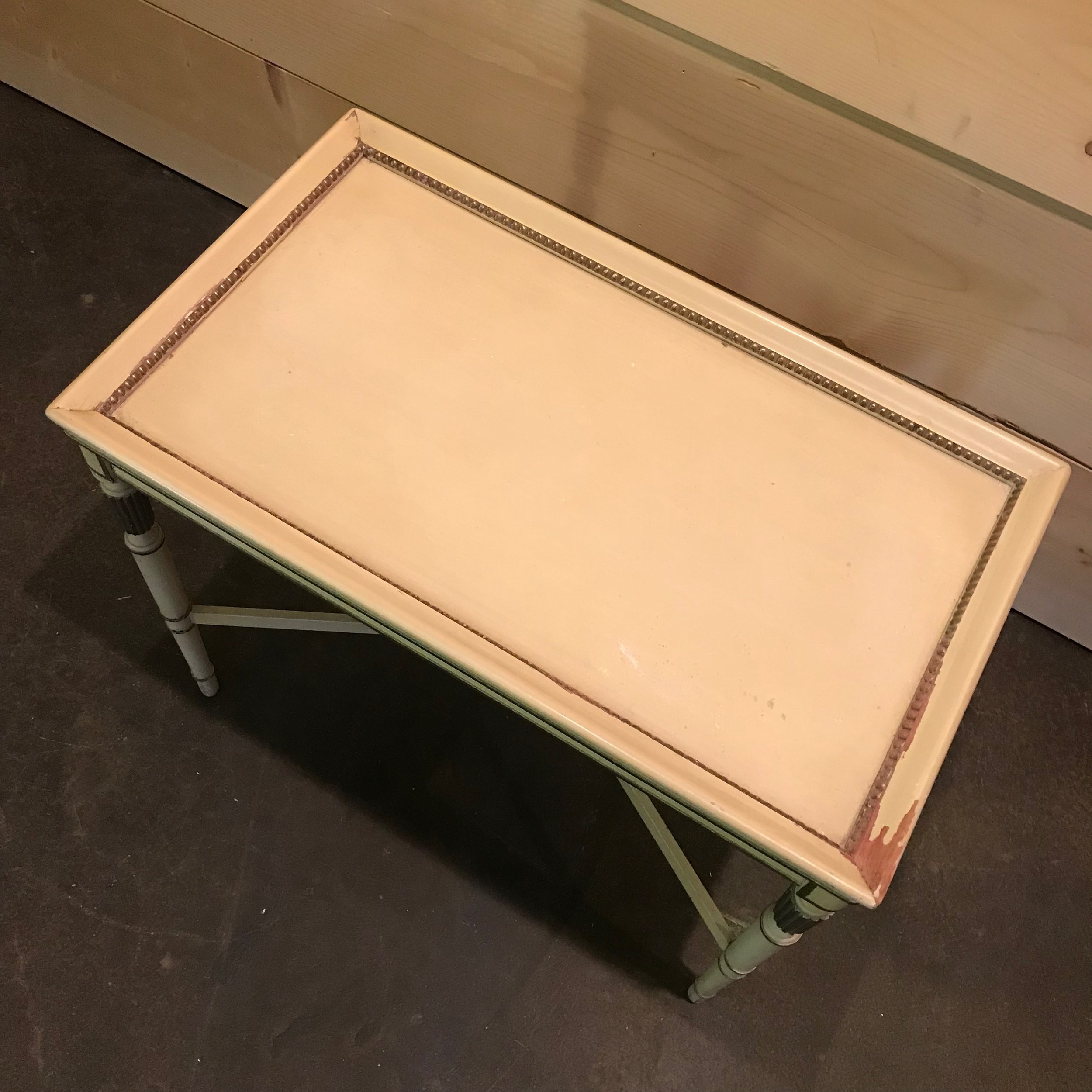 Hollywood glam side table in off-white with gold leafing. vintage furniture to rent.