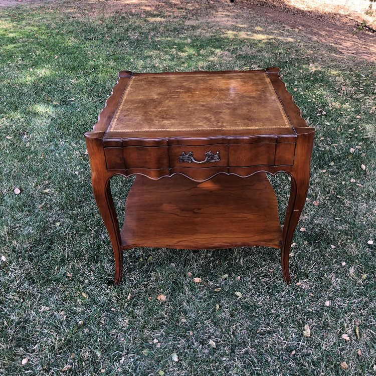 """Sadie   Scalloped, leather top table with one drawer. Gold details on the leather. Shelf on the bottom. 27"""" square x 25"""" high."""