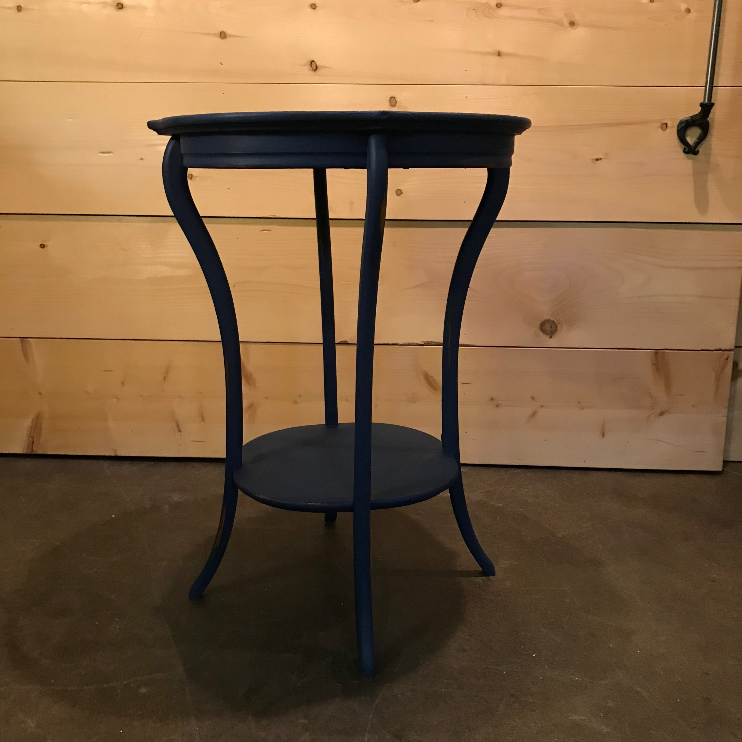 """Barry   Small round side table with a shelf on the bottom. Chalk painted navy blue. 20"""" tall x 22"""" round."""