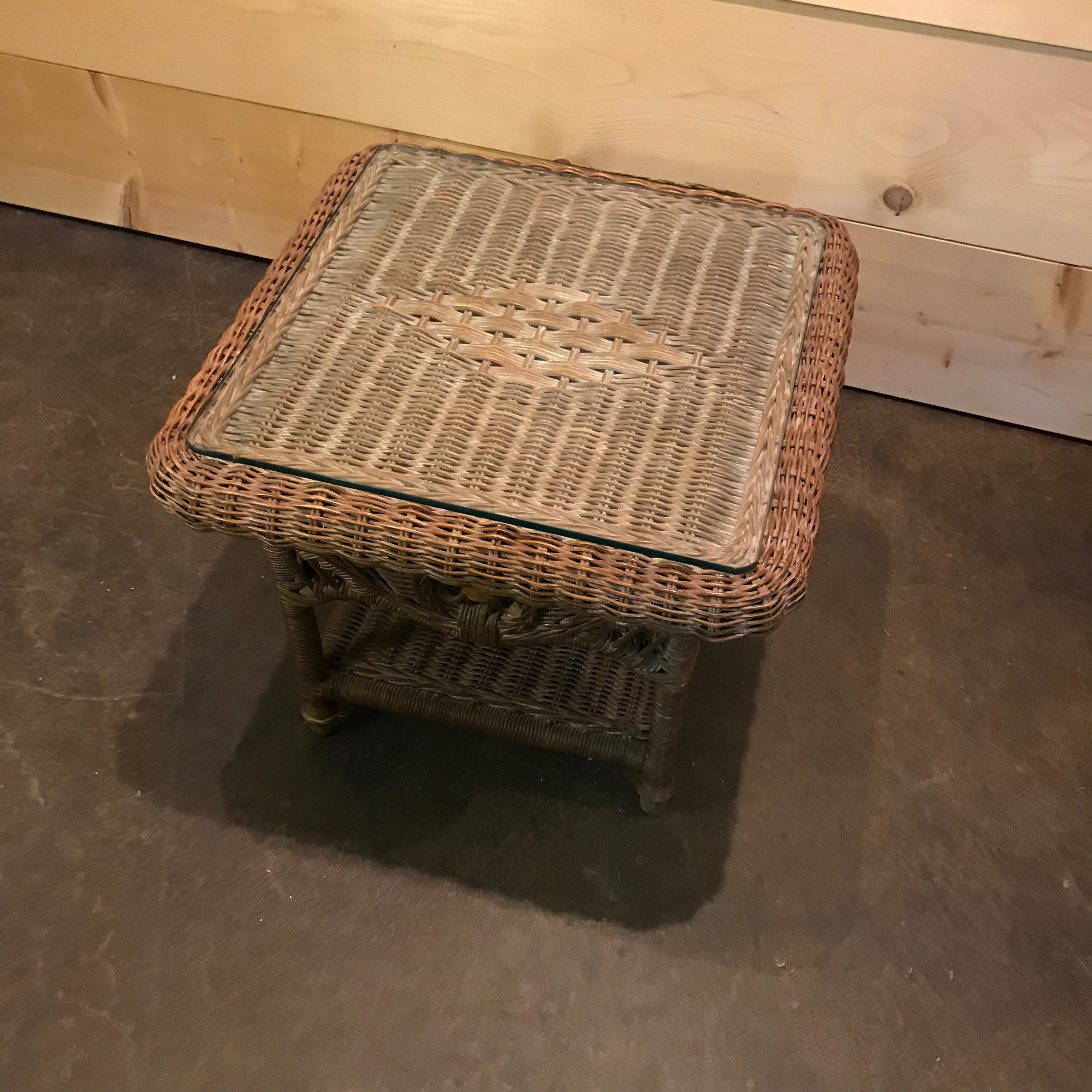 Wicker side table with patterned top and bottom shelf. Vintage furniture rental