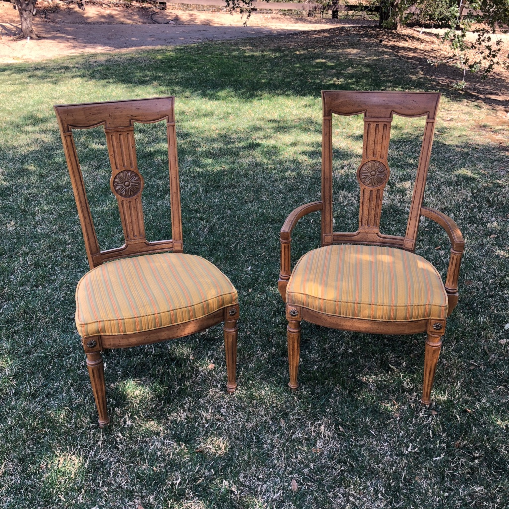 "Clementine and Carmello   Mid-century modern dining chairs with green, orange, and gold striped attached cushions. Flower medallion inlay with spindle legs. Two with arms, four without arms. 39"" high x 20.5"" wide."