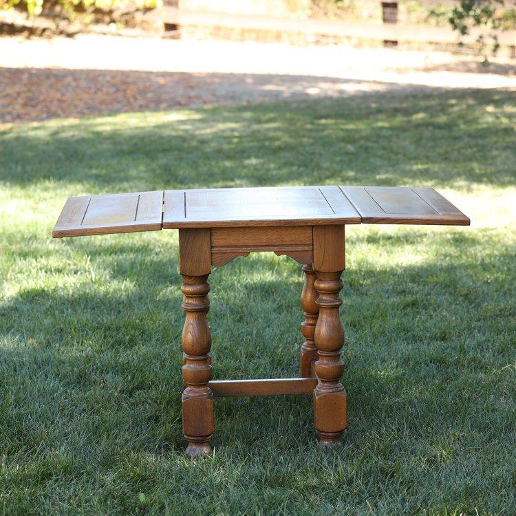 Vintage drop side table with spindle legs. Rental.