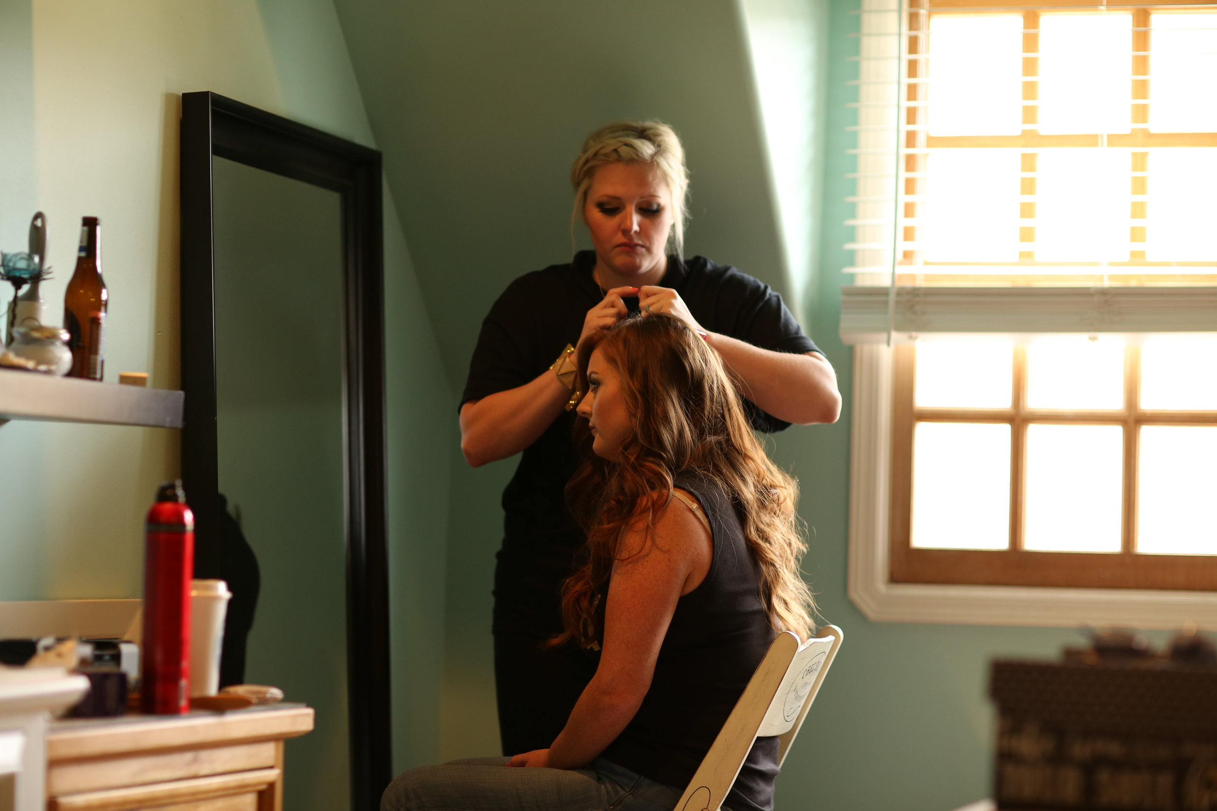 Professional hair dresser working on styling a French braid hairstyle for the bridesmaid of the wedding party in Murrieta California at Chateau Adare.