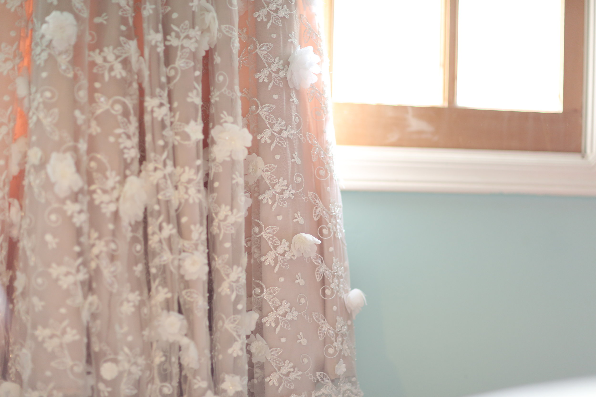 Custom made wedding dress with three dimensional flowers sewn on by hand on the lace. A Sew Kelly creation.
