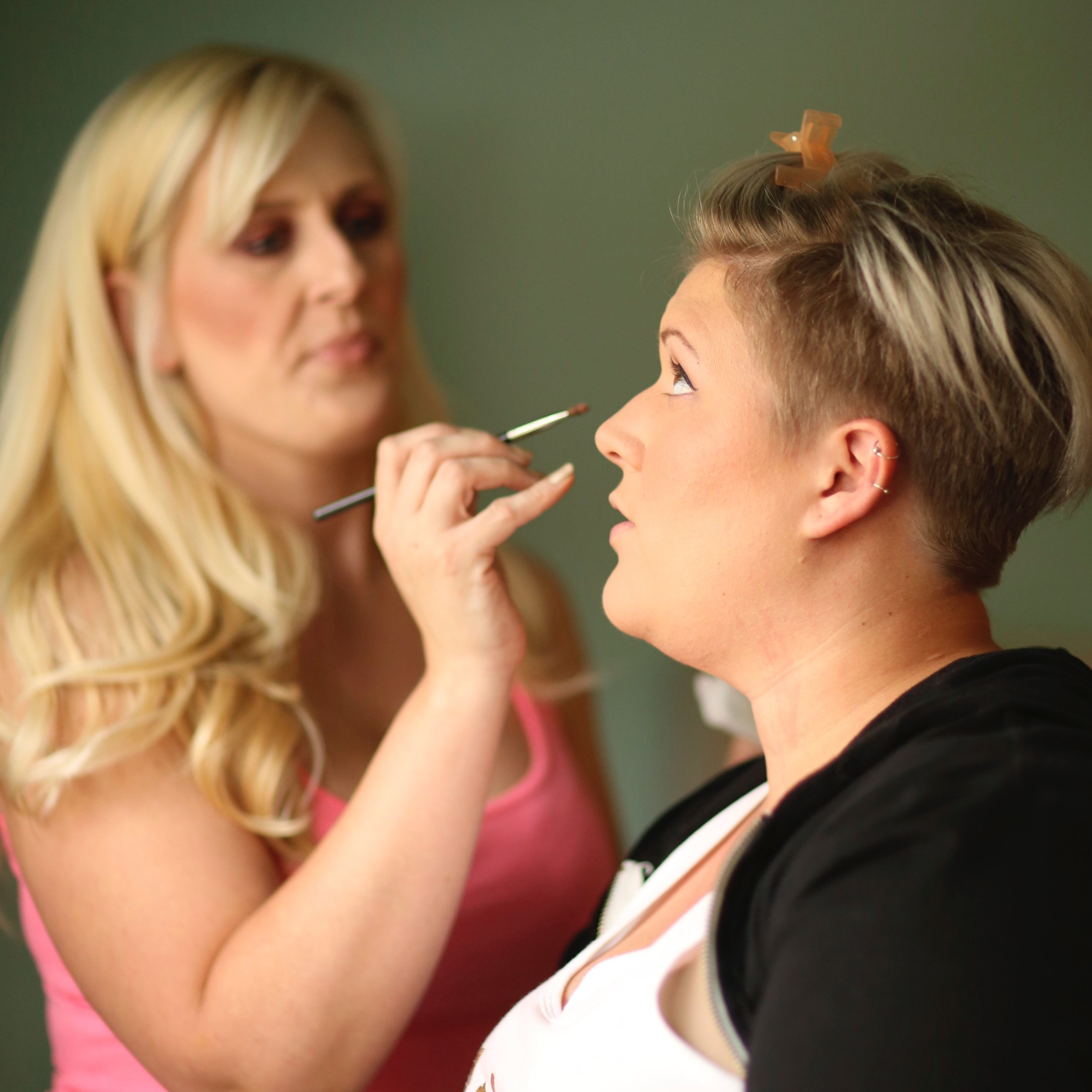 A professional make up artist applying make to a bride on her wedding day.