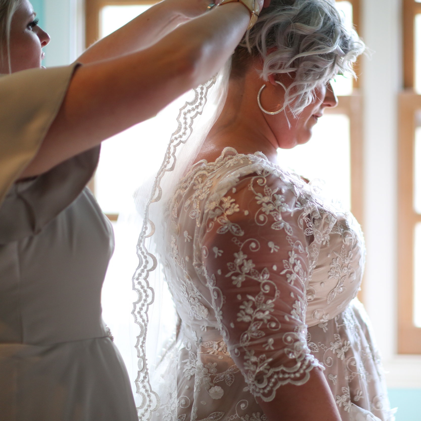 Bridesmaid putting the veil on the bride as she helps to finish getting her ready for her walk down the aisle in Murrieta California.