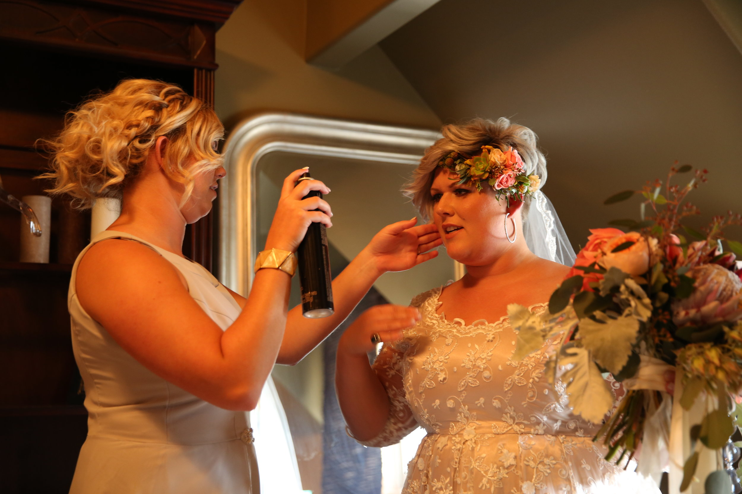 Bridesmaid putting one last spritz of hairspray on the bride just before she walks down the aisle on her wedding day.