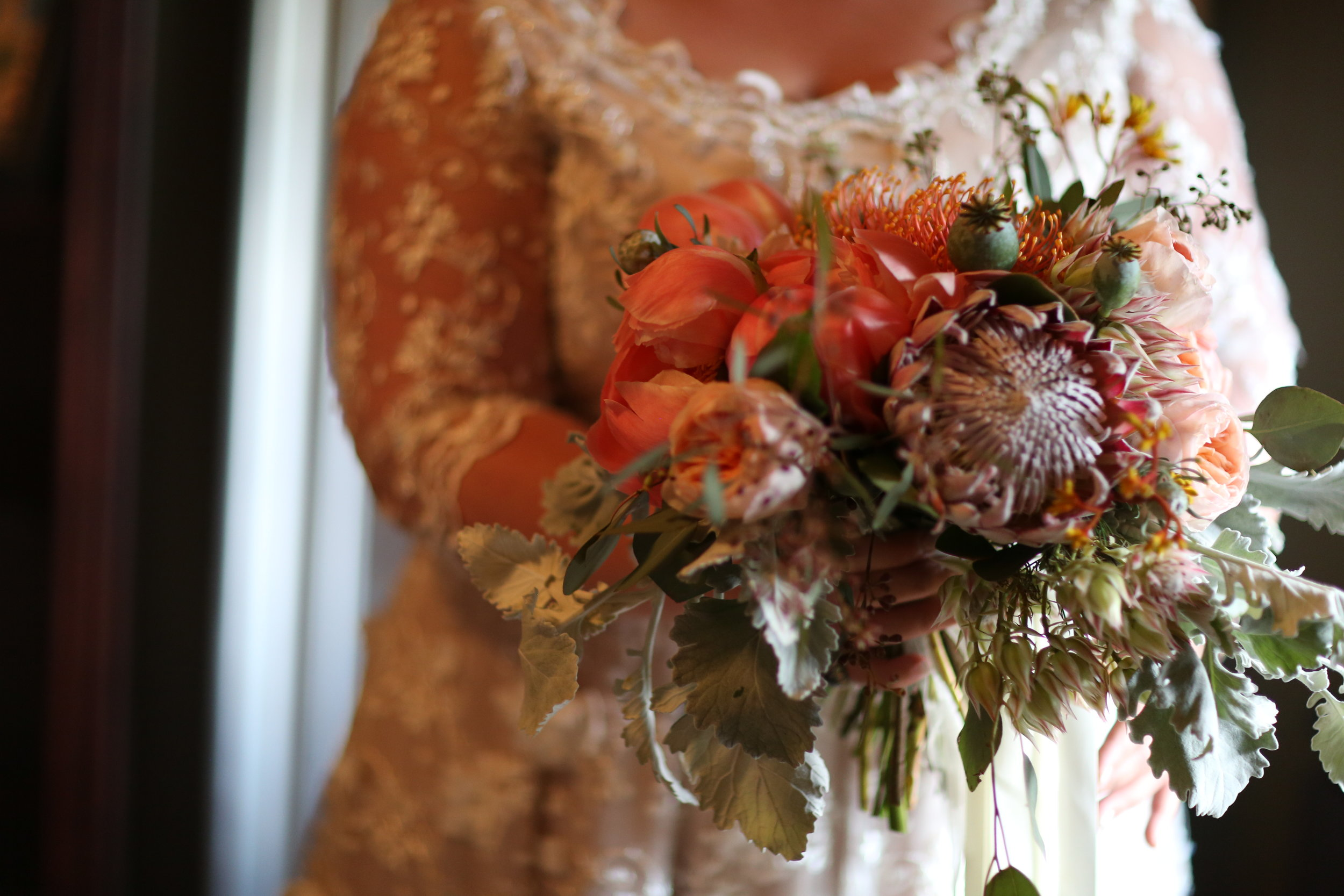 Coral bridal bouquet with king protea and peonies. Bride holding it.