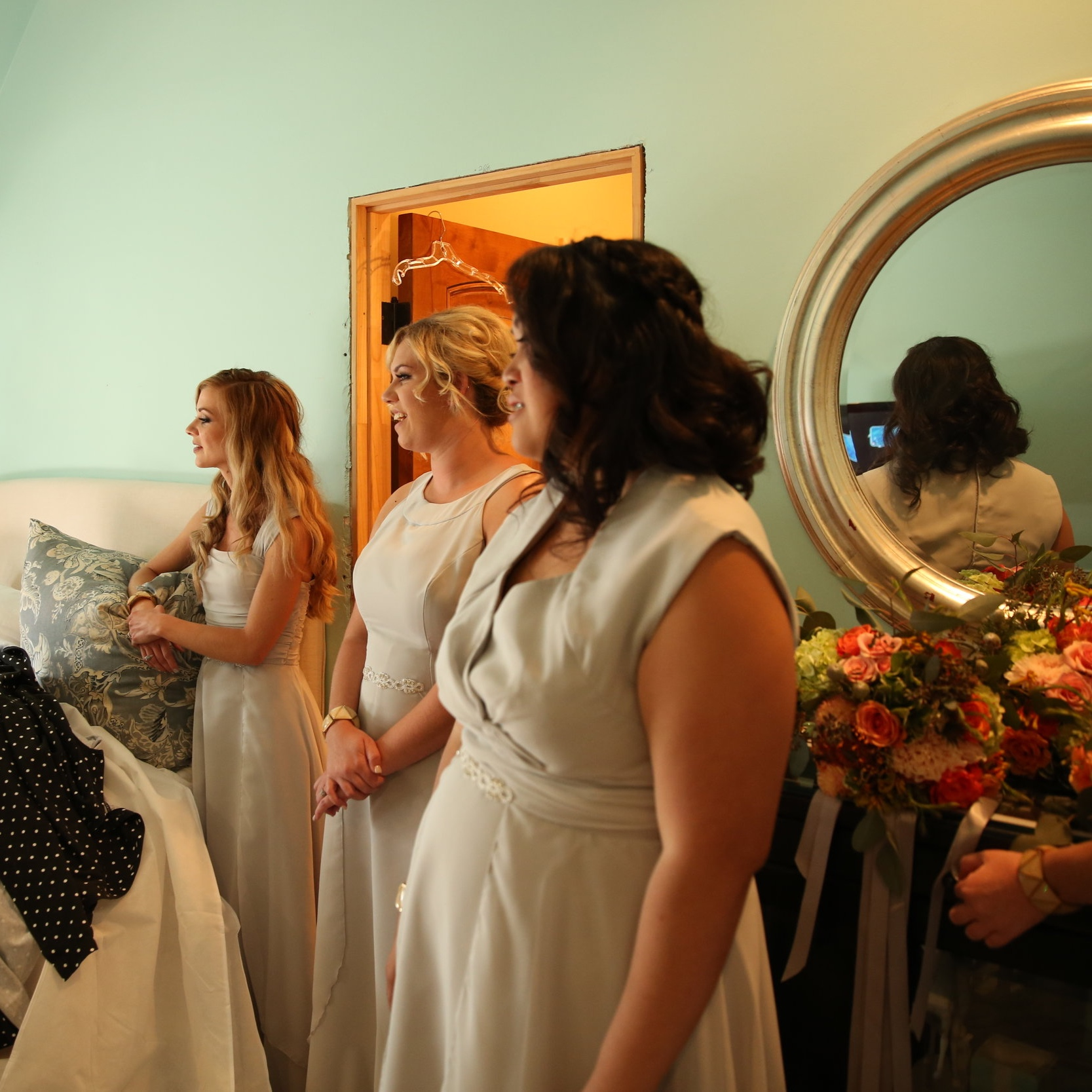 Bridesmaids gaze at the bride as she puts on her wedding dress while they all get ready for the wedding ceremony.