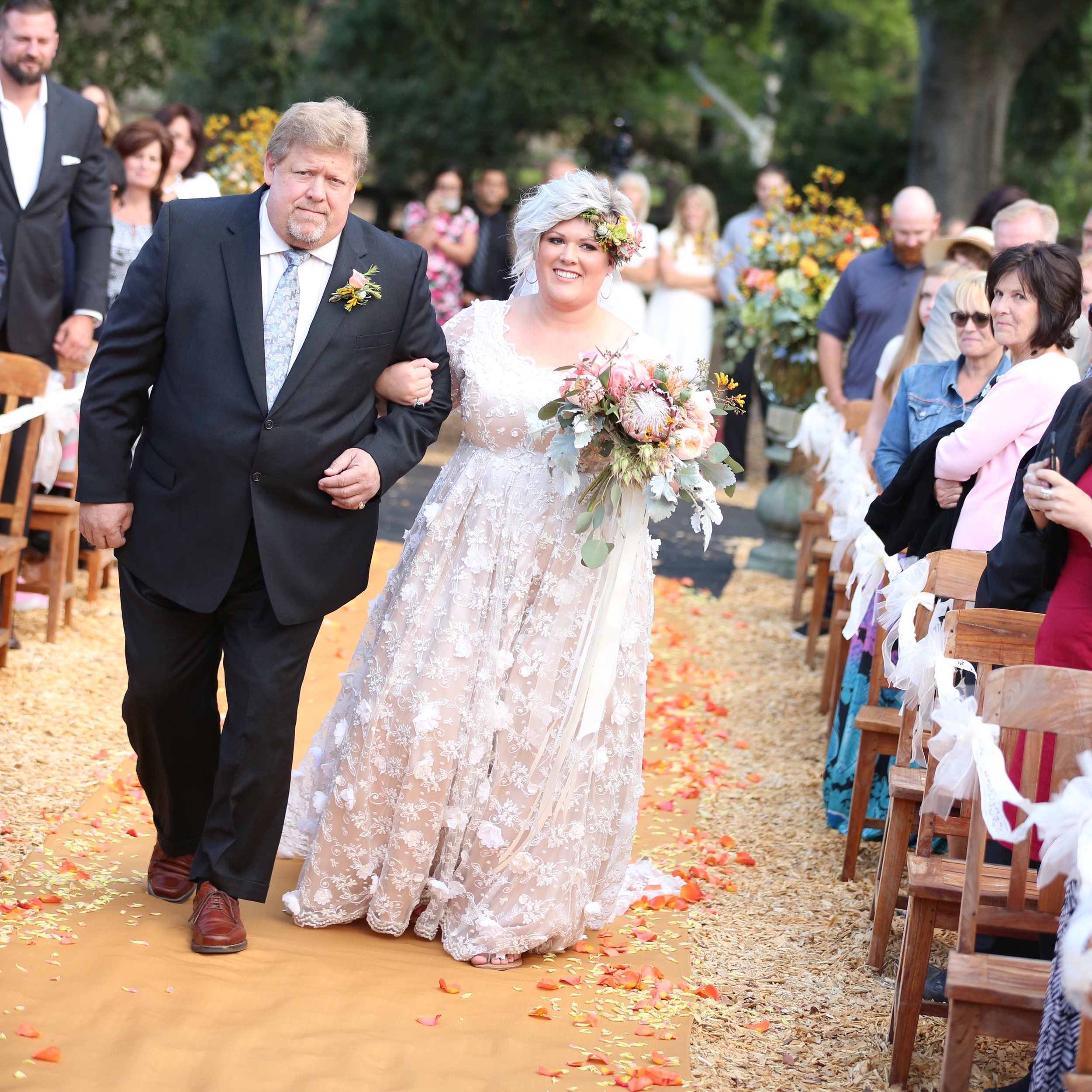 The father of the bride walking her down the aisle on her wedding day at Chateau Adare in the Temecula Valley.