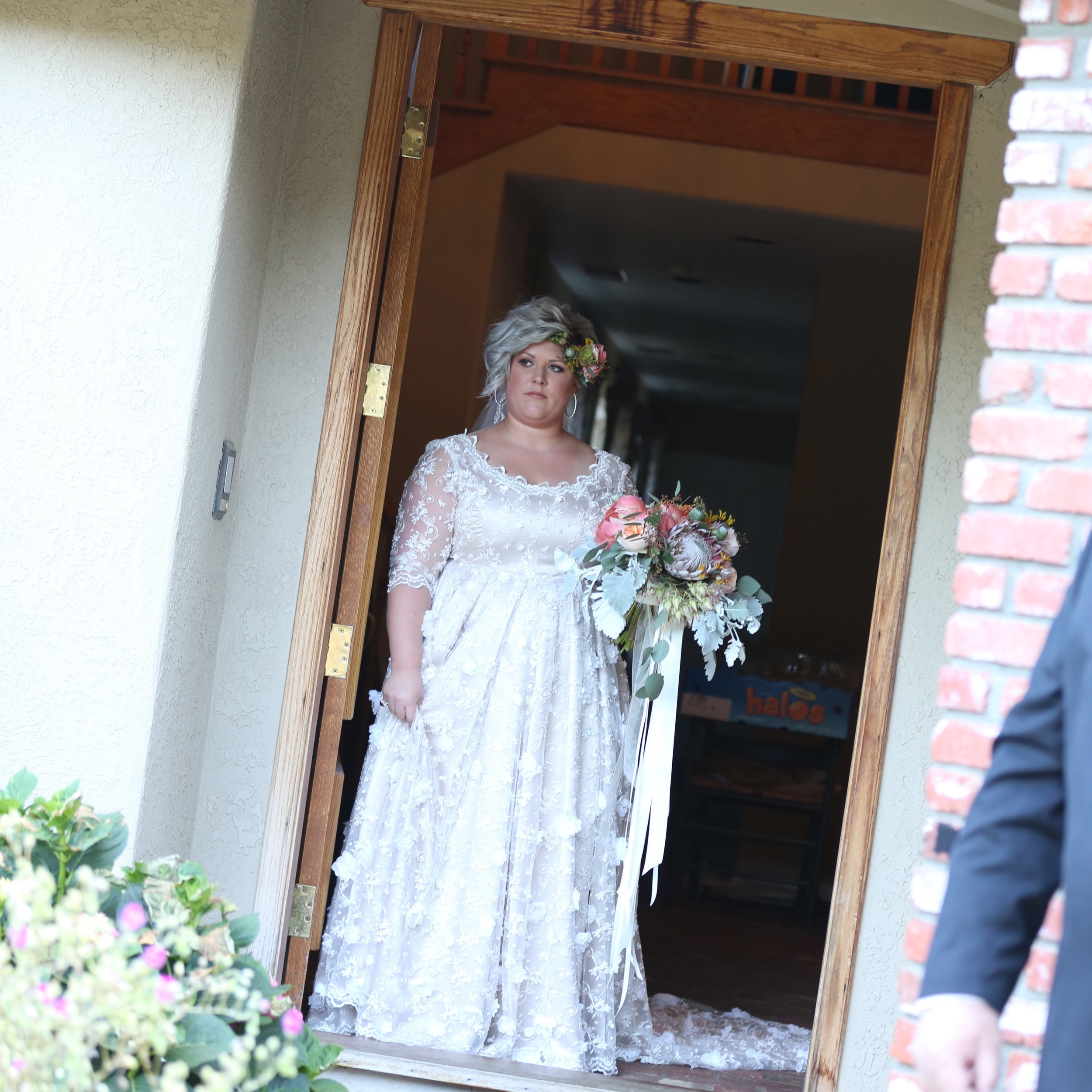 The bride waiting in the doorway for her father to walk her down the aisle on her wedding day.