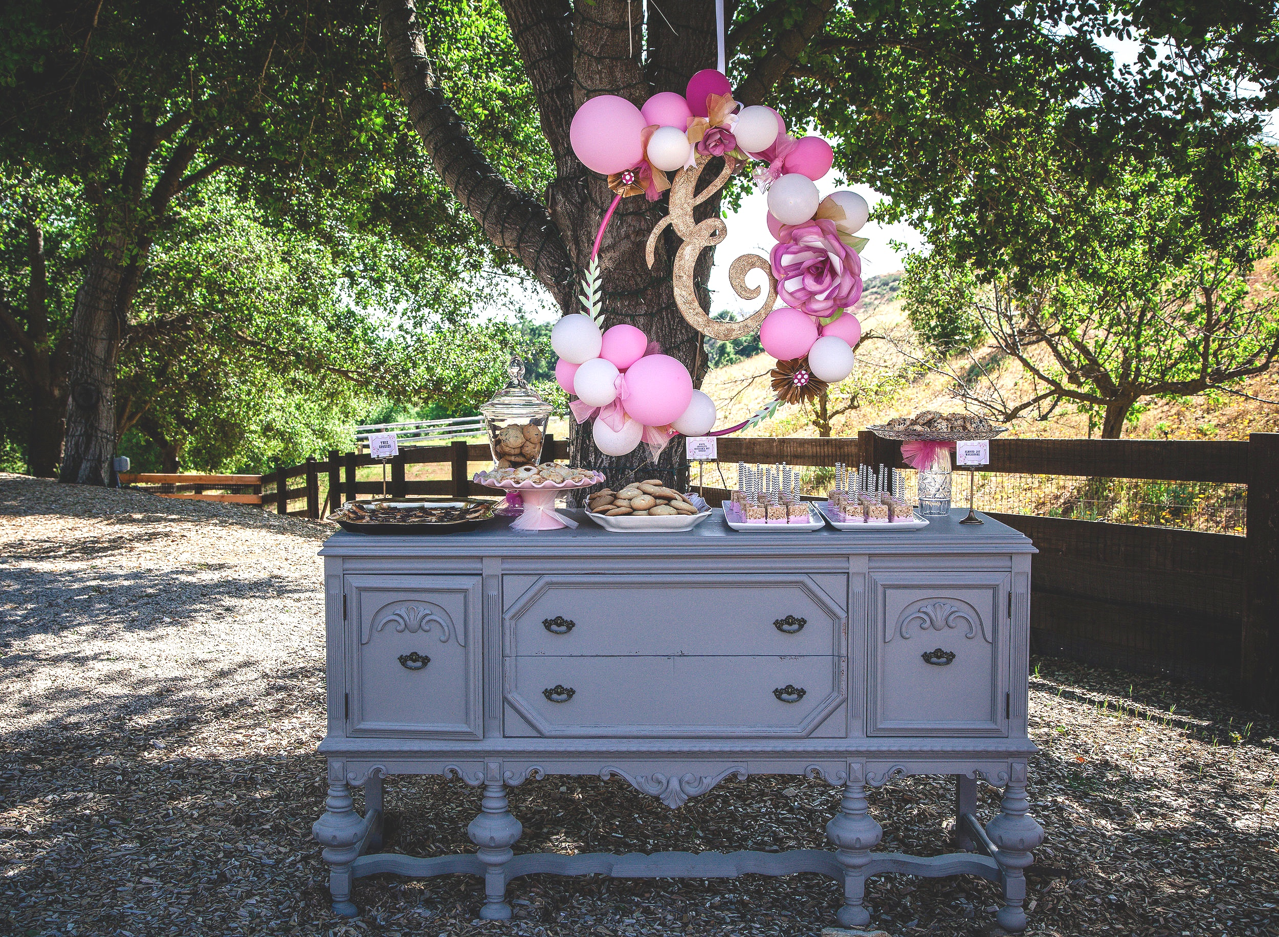 Grey vintage buffet with balloon hanging feature. Desserts on the buffet made in the Temecula Valley.