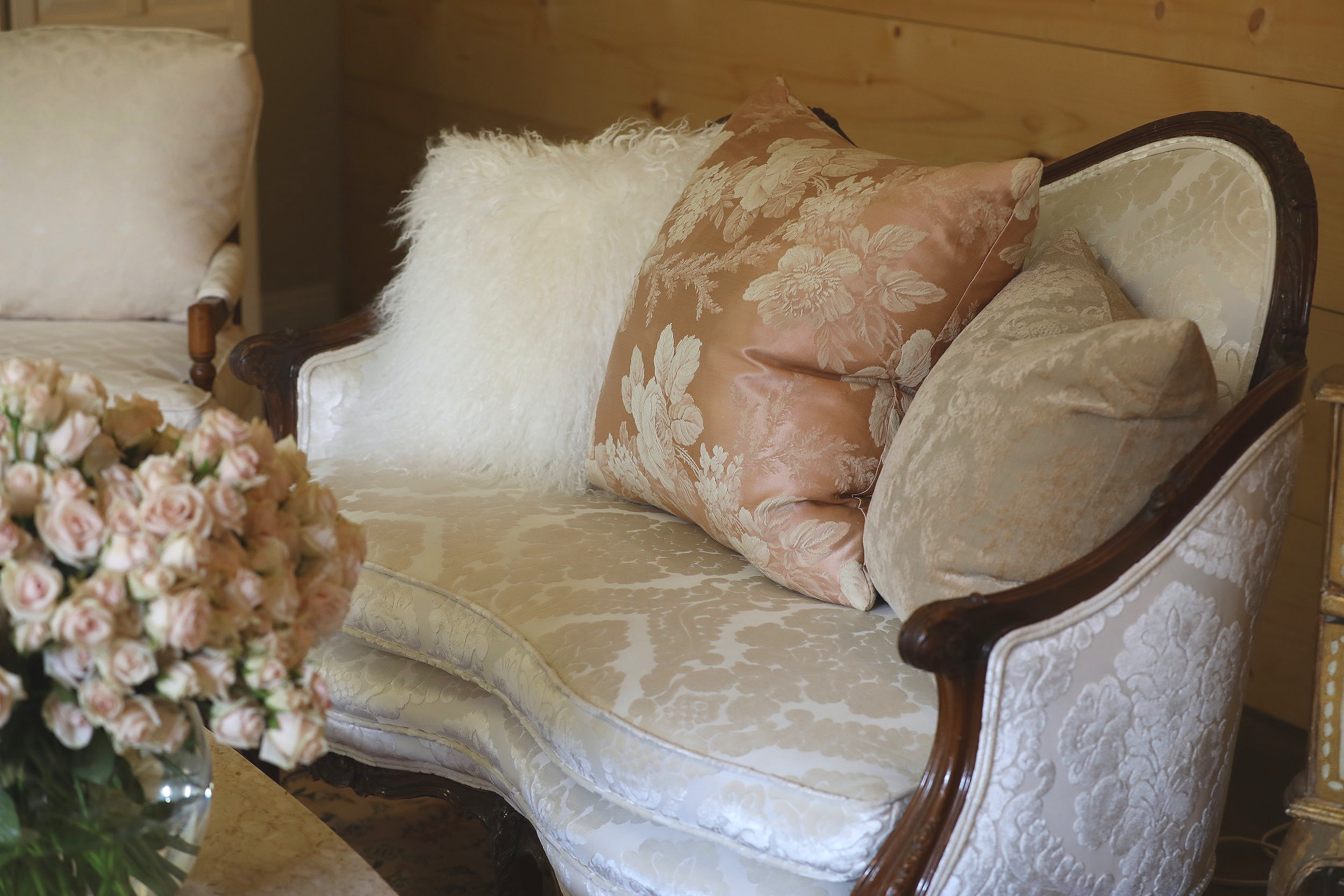 Pink overstuffed pillows lining a white couch with a white coffee table at a venue in the Temecula Valley.