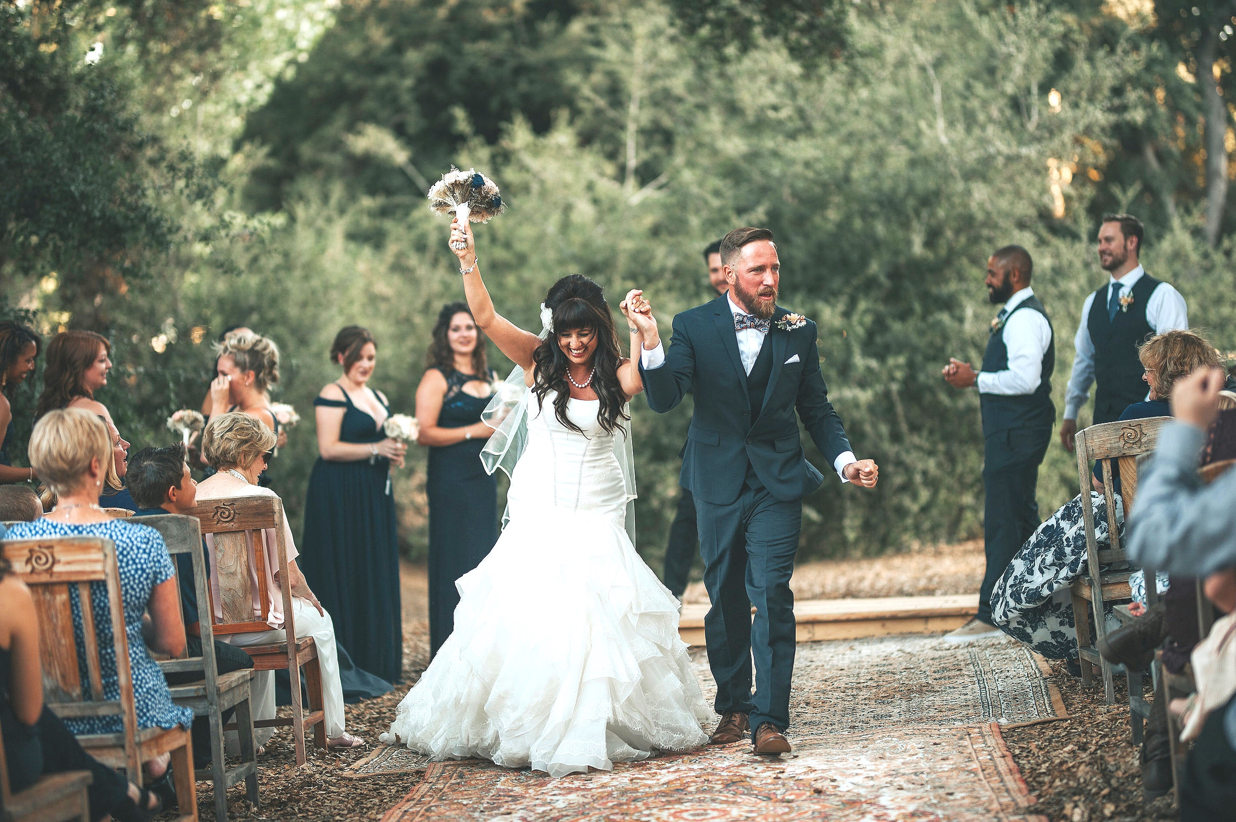Bride and groom walking down the aisle made of vintage rugs in the Temecula Valley.
