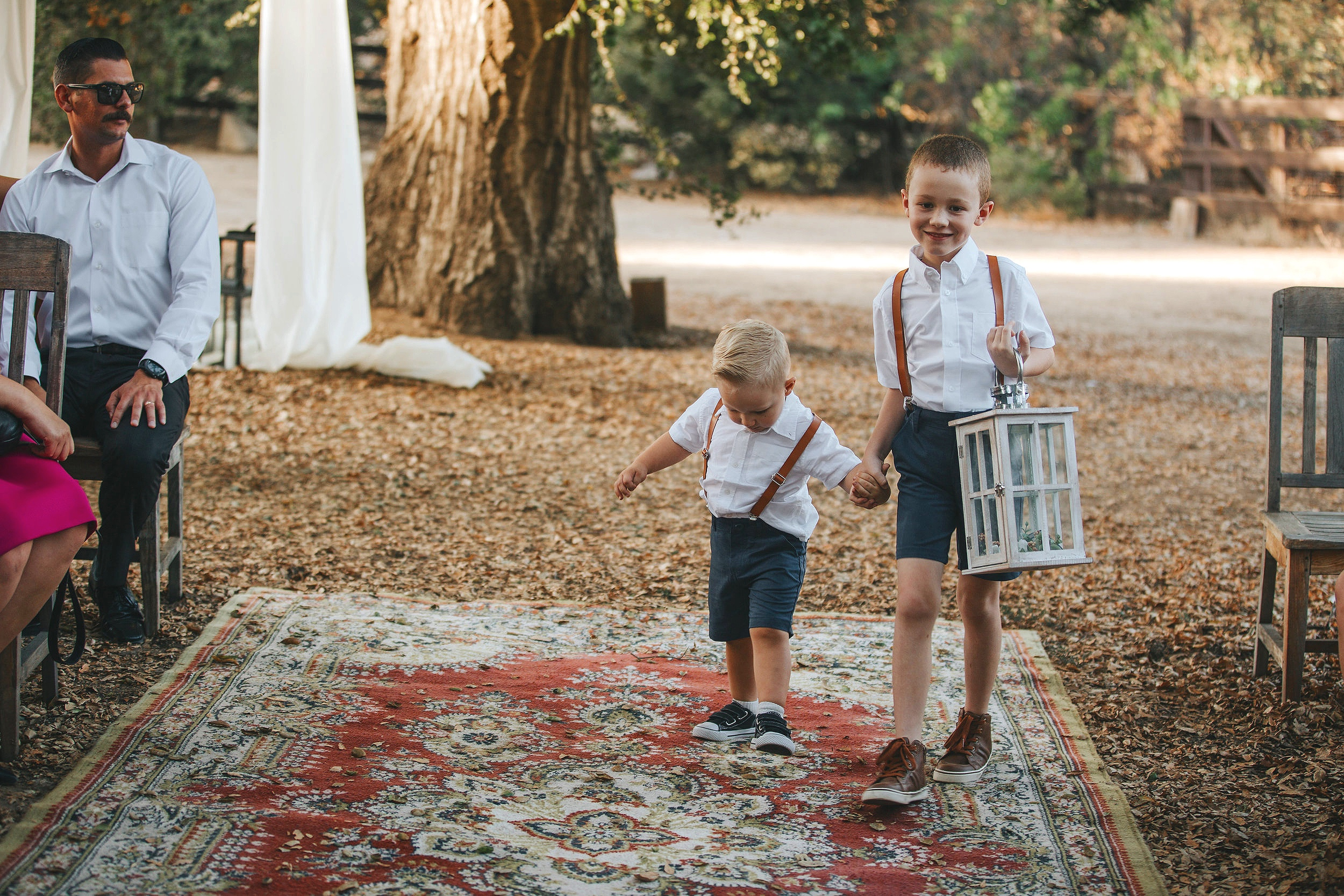 Walking down a wedding aisle of rugs, these cute ring bearers are having loads of fun. wedding at Chateau Adare in the Temecula Valley.