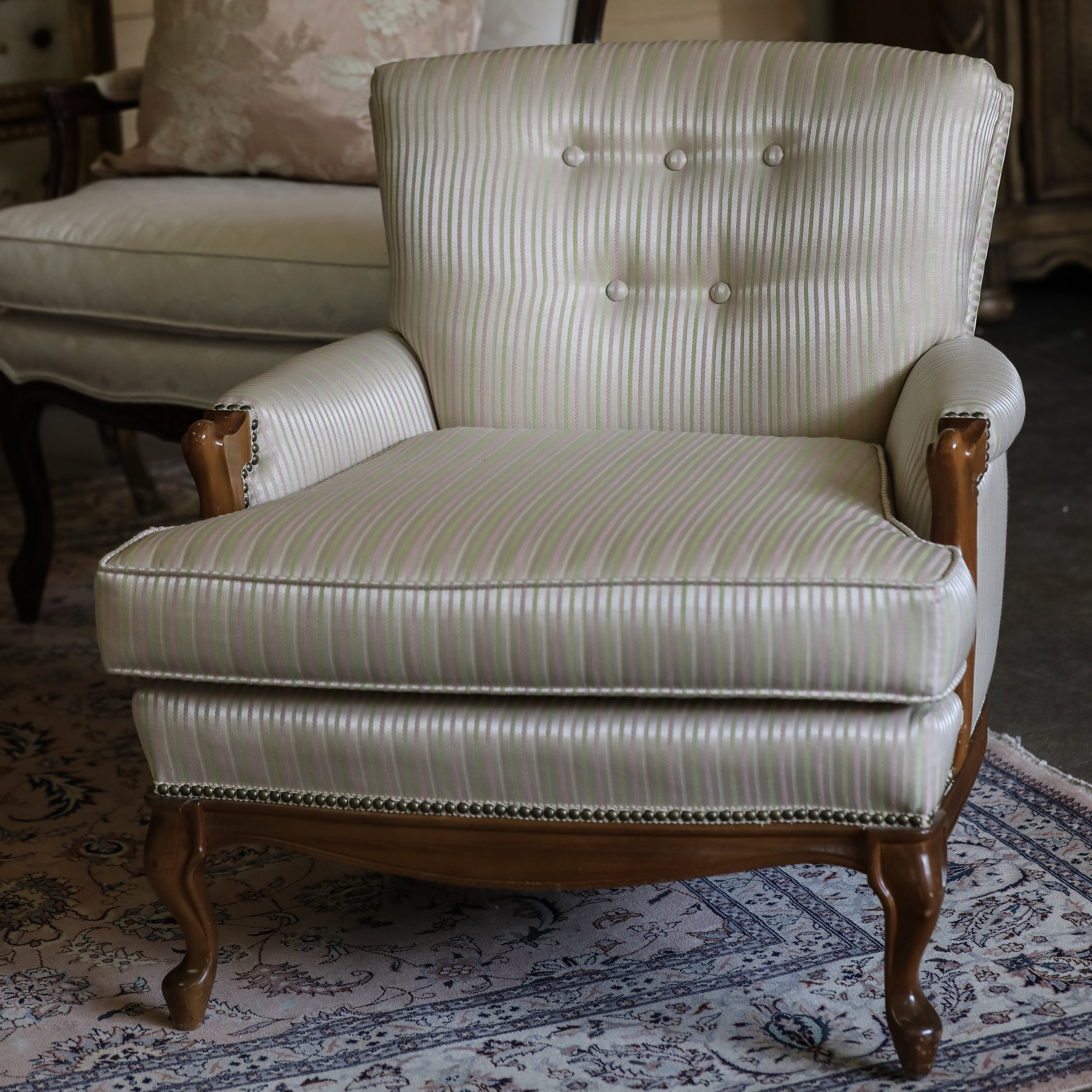 Jeanne  Pink striped club chair with tufted back.