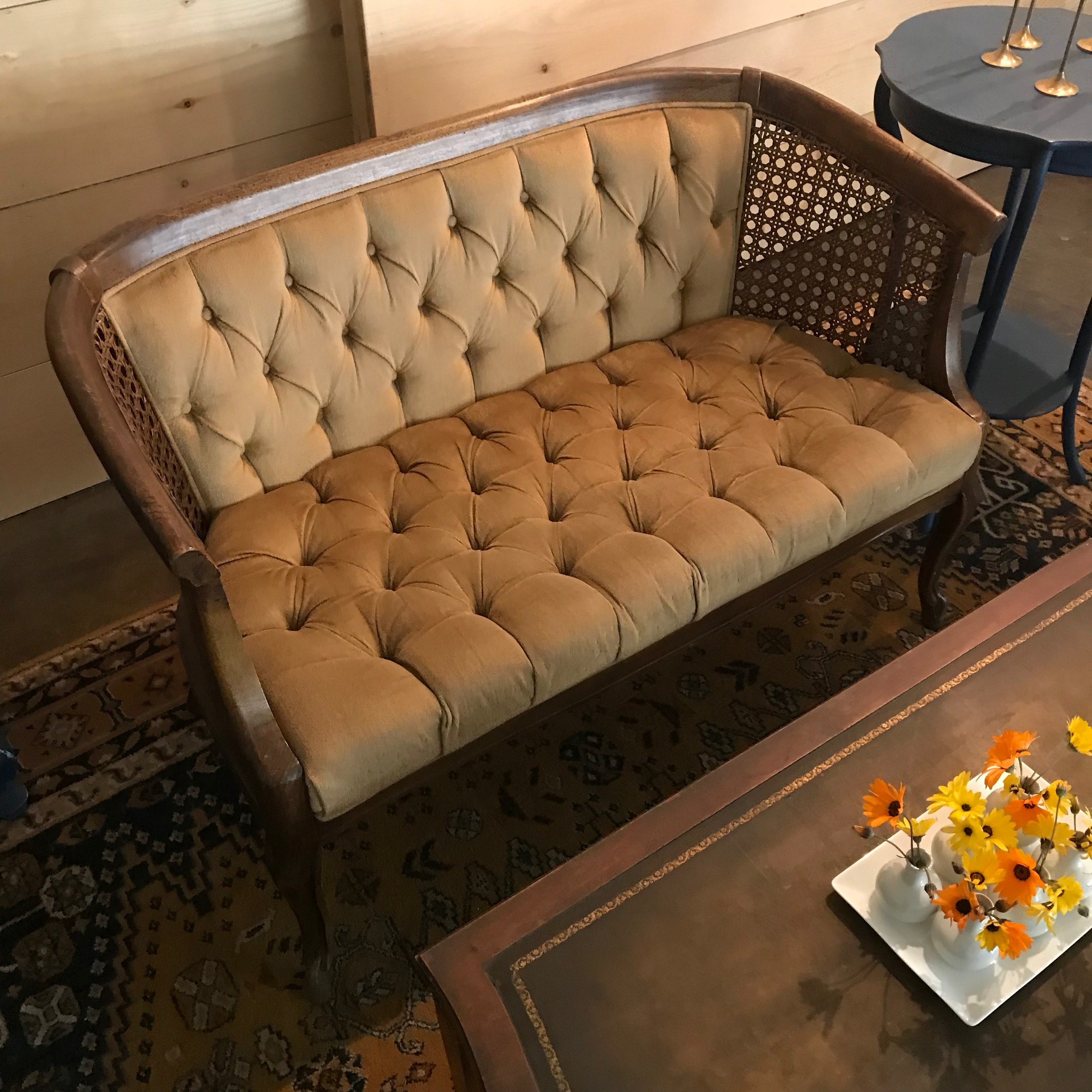 Quinn   Vintage gold velvet loveseat with tufting on the seat and the back.  Caning on both sides of the seat.