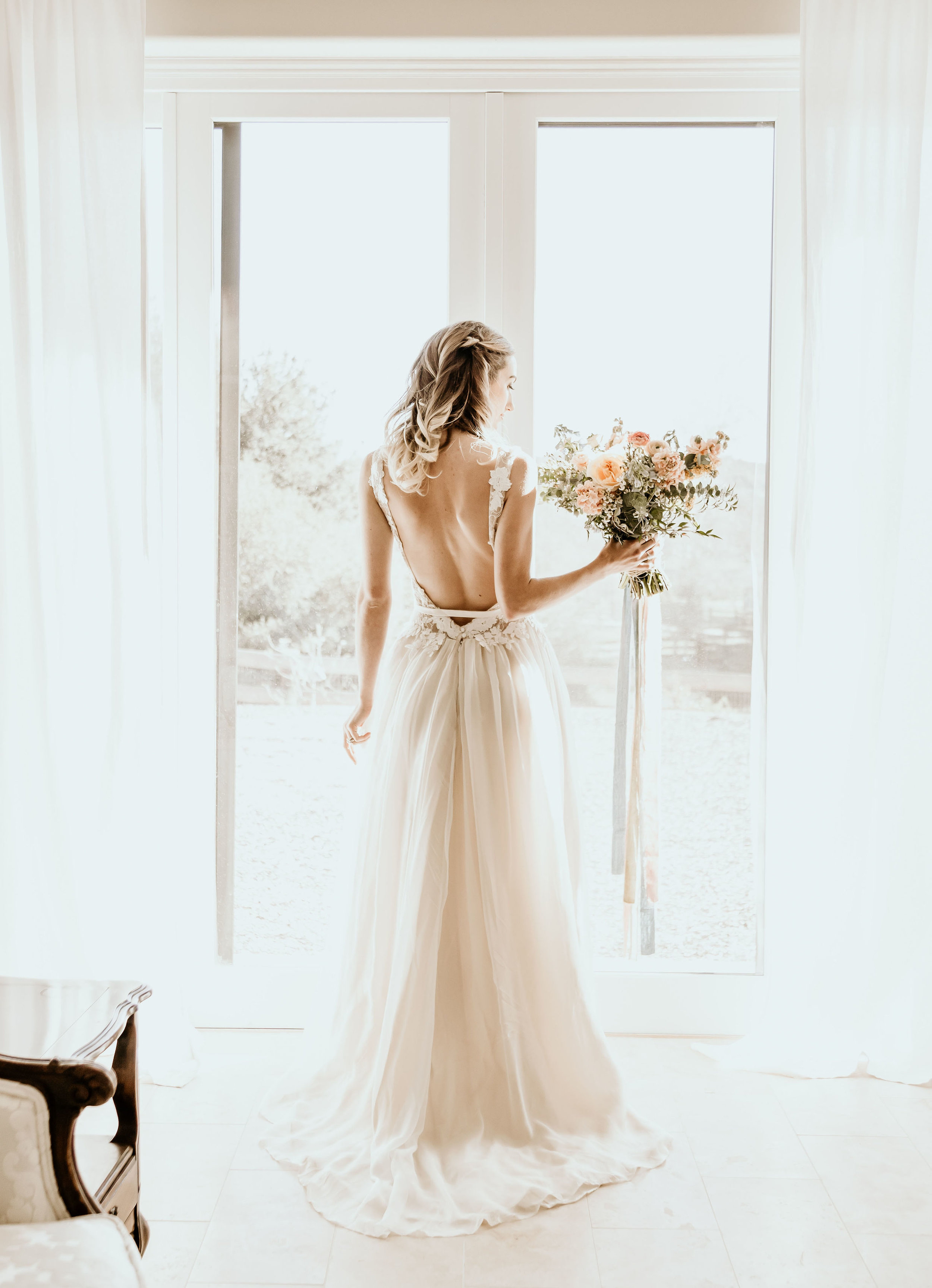 Alice in Wonderland bride standing in front of the sliding glass door in the bridal suite at Chateau Adare in Murrieta.