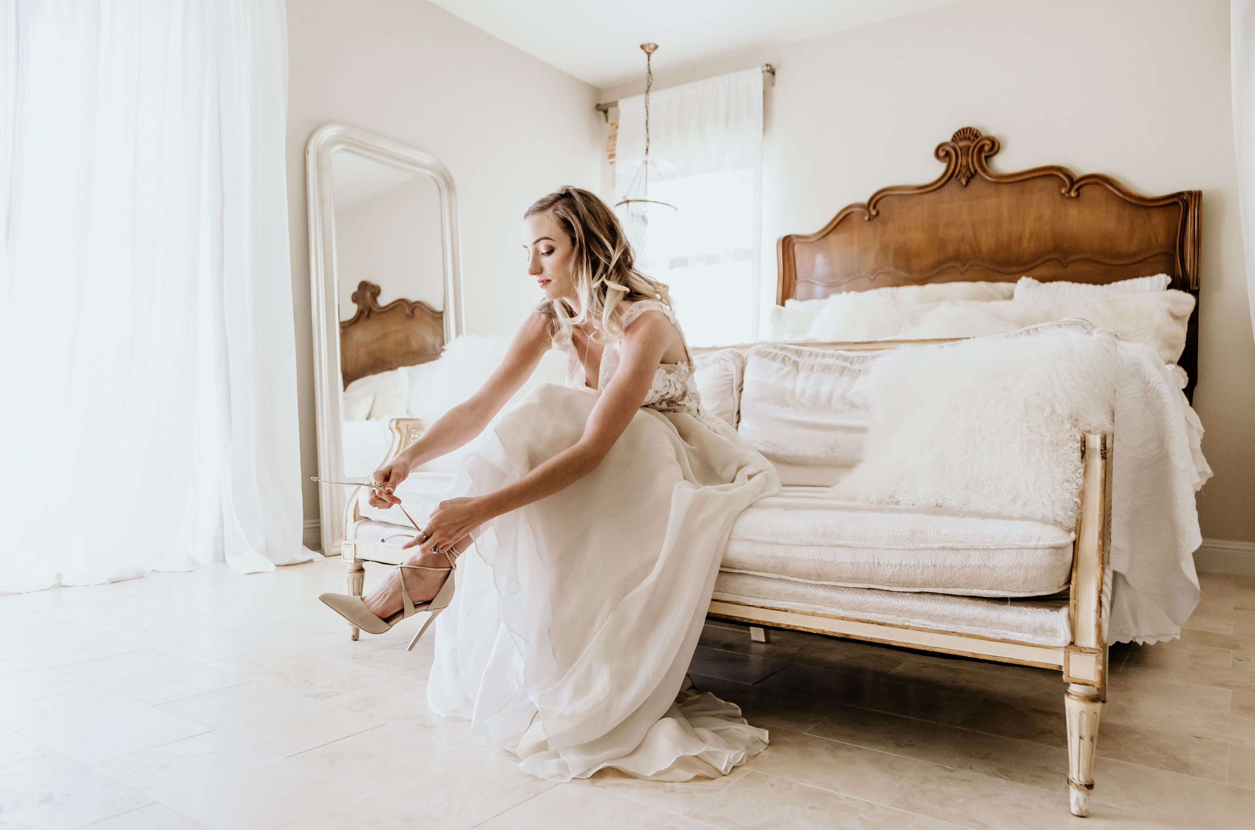 Alice in Wonderland bride in the bridal suite at Chateau Adare in Murrieta putting on her shoes. She is sitting on a vintage couch from Birdie in a Barn in Murrieta.