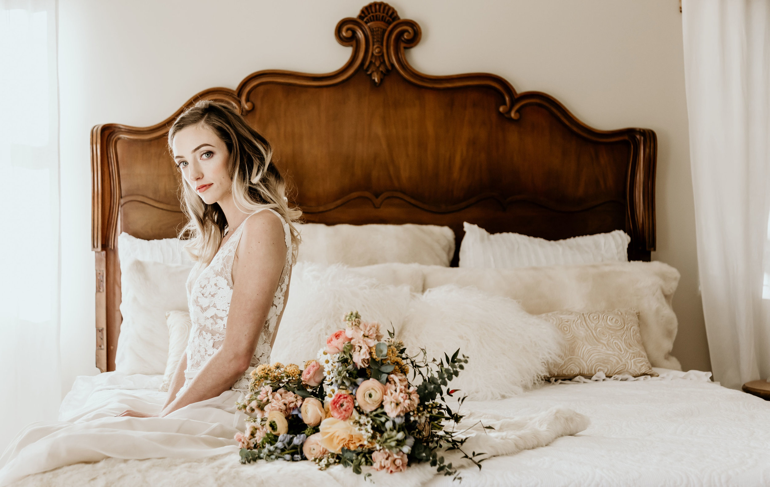 Alice in Wonderland bride sitting on the vintage white bed in the bridal suite at Chateau Adare in Murrieta.