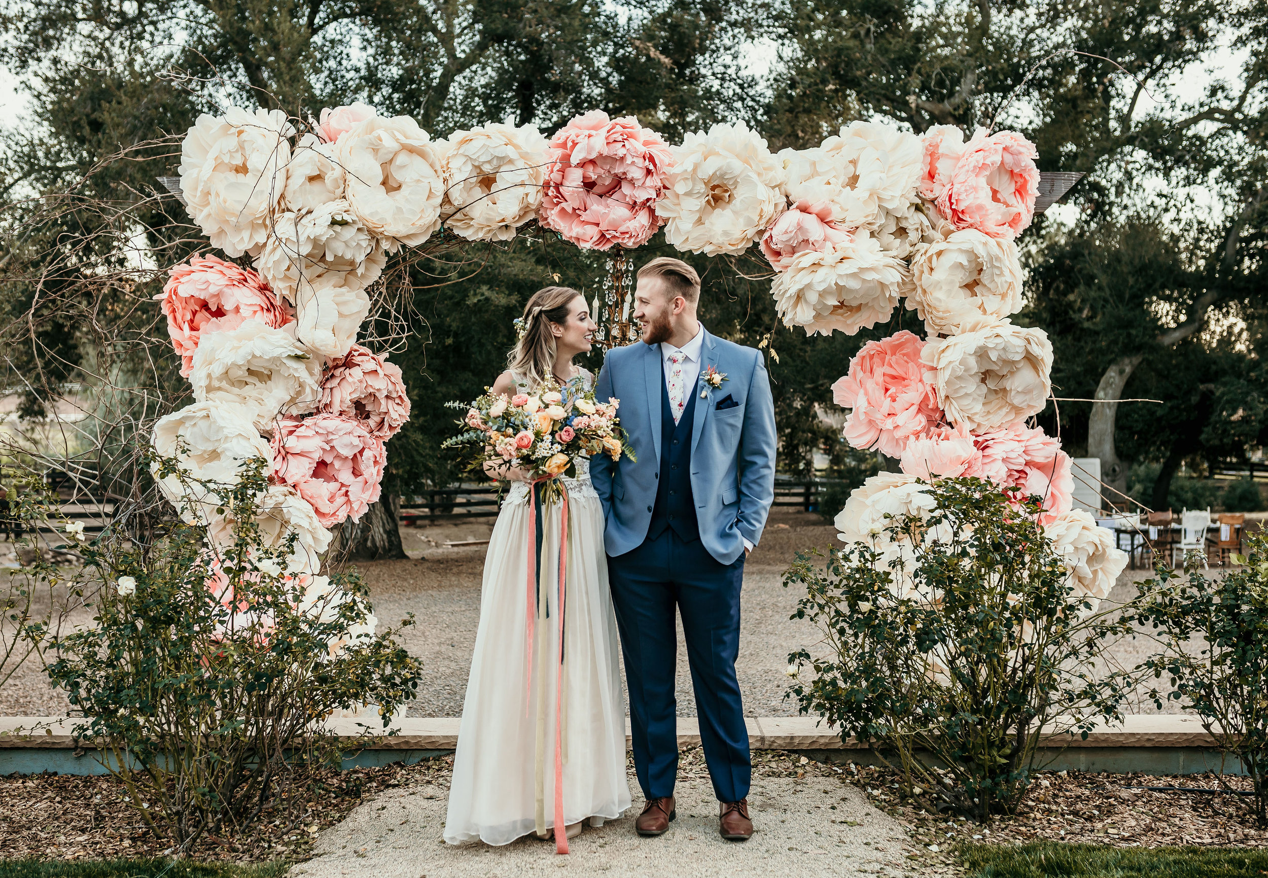 Alice in Wonderland bride and her groom standing in front of the large wooden arch at Chateau Adare in Murrieta. The arch is decorated with large handmade paper pink and white peonies.