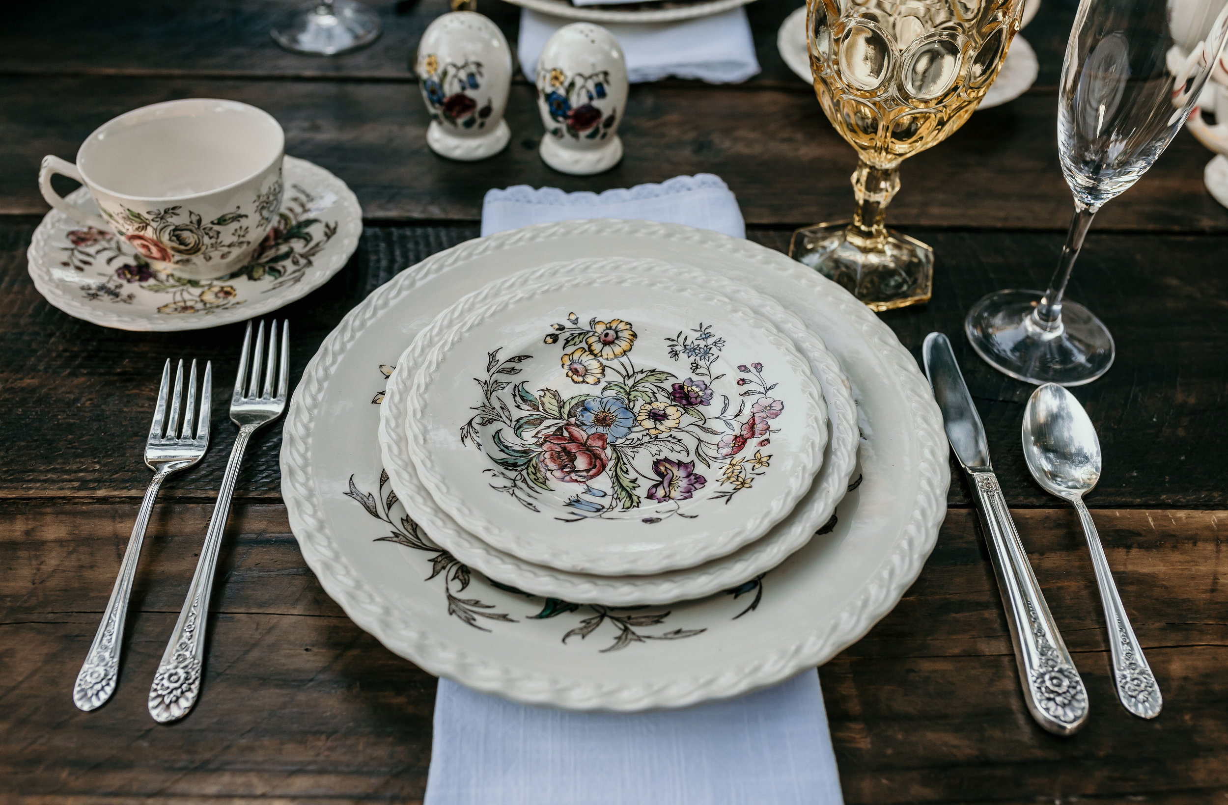 Vintage Johnson Brothers china set on a farm table with vintage goblets and silverware. This was used in the Alice in Wonderland styled shoot at Chateau Adare in Murrieta.
